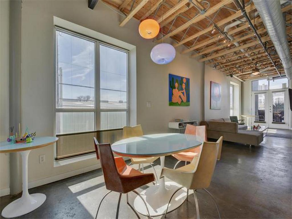 Long industrial style loft with exposed ductwork, mod furniture