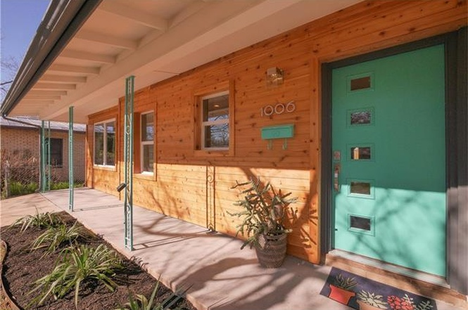 close-in shot of midcentury house with new, rustic wood siding, aqua door and porch posts