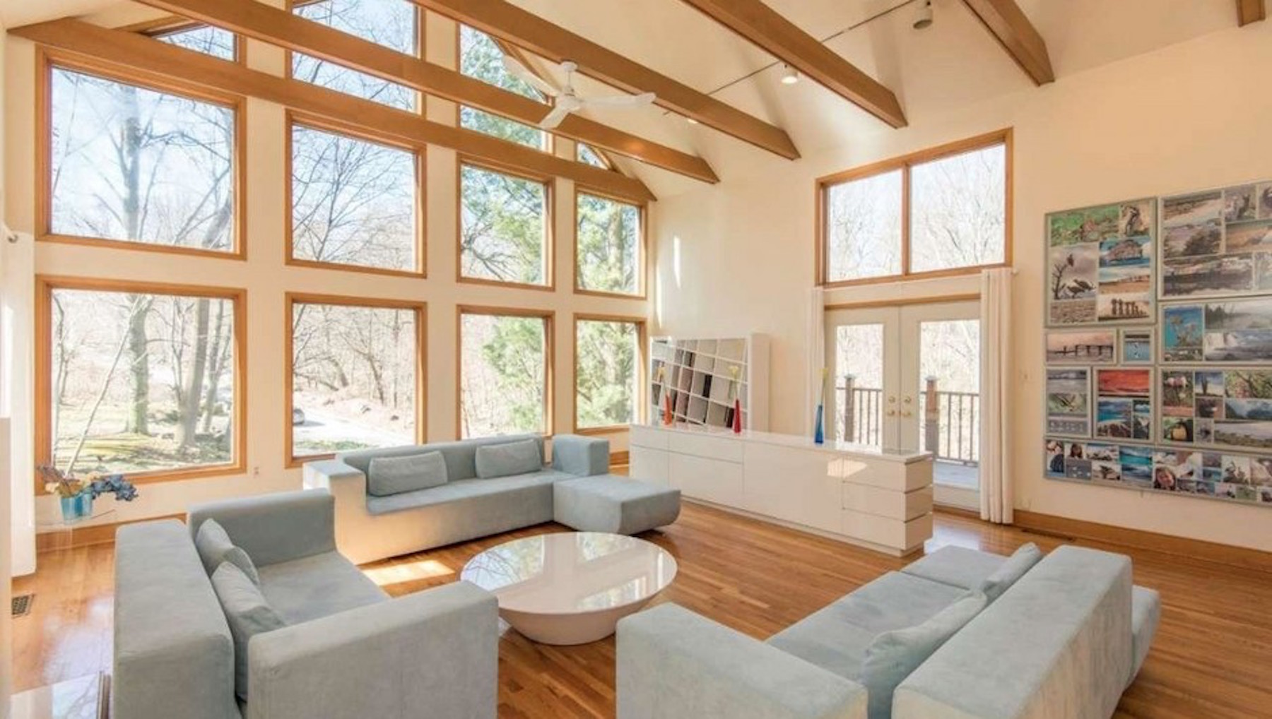 A large two-story living space with exposed beams, hardwood floors, and a wall of windows.