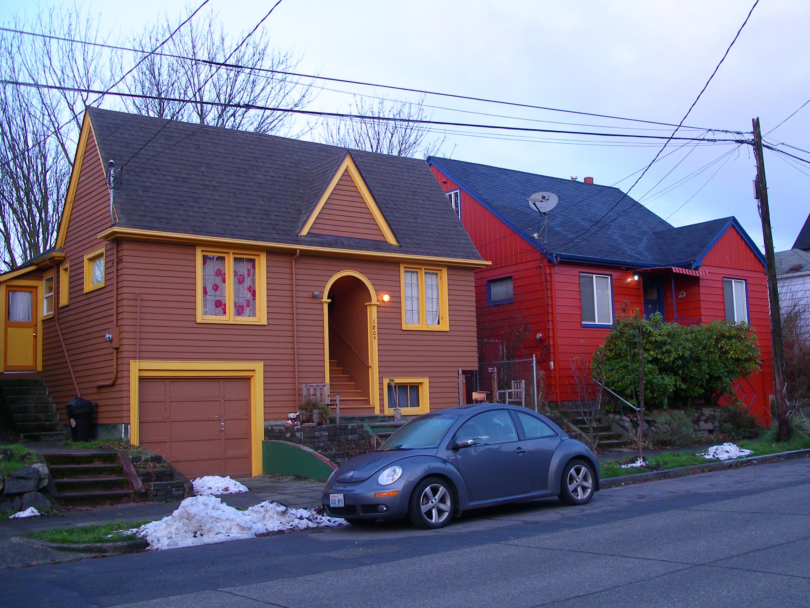 Two houses shot from the street, one brown with gold trim, the other red with blue trim. The brown house is closer, and has an arched entryway.