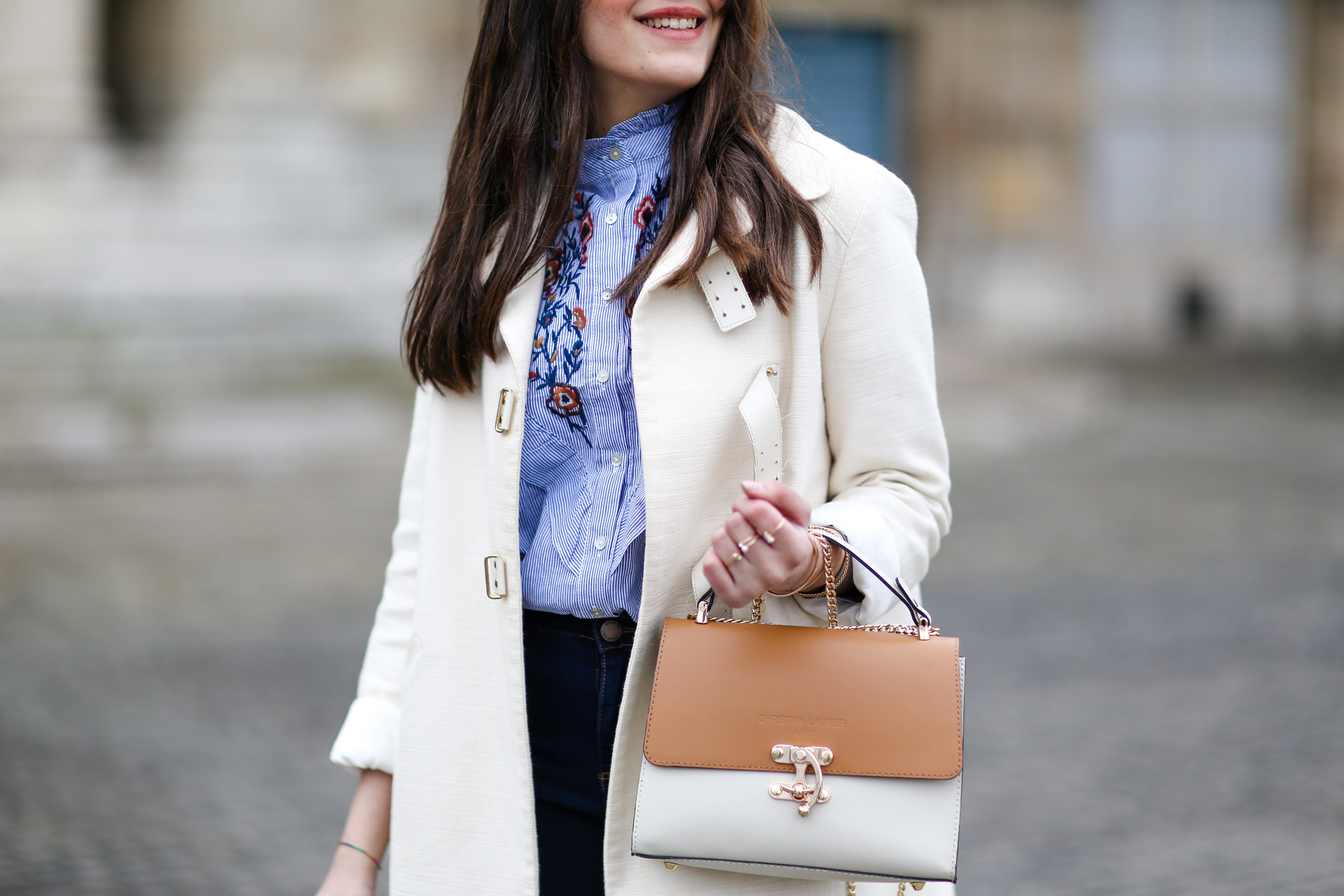 Woman in a blue button-down shirt under a white jacket. She carried a white and tan bag.