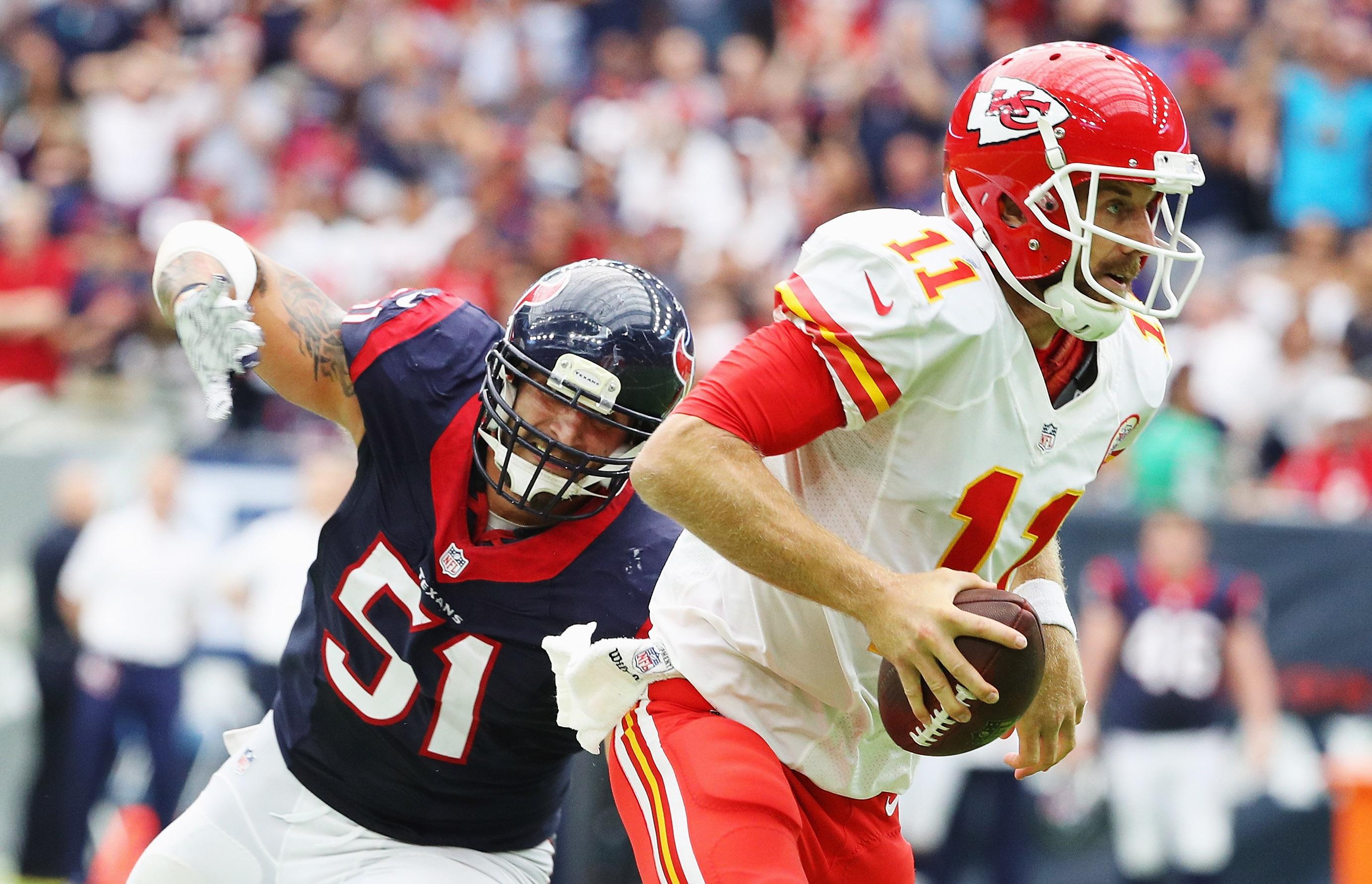 HOUSTON, TX - Kansas City Chiefs quarterback Alex Smith (11) tries to evade Houston Texans pass rusher John Simon (51) before being sacked at NRG Stadium.