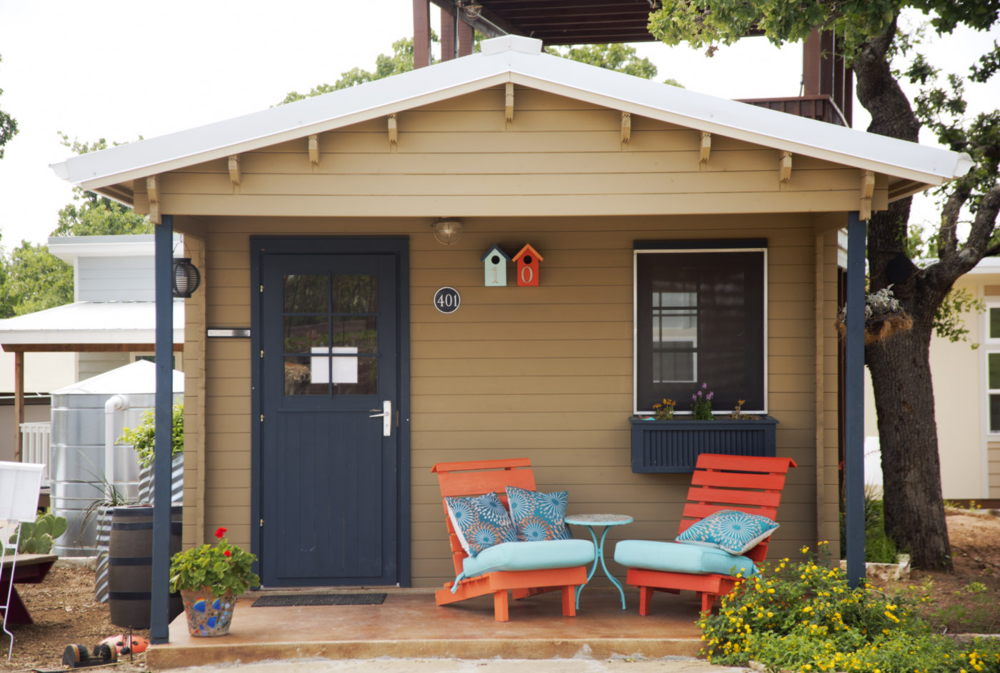 A brown tiny house with peaked roof, small porch, red chairs