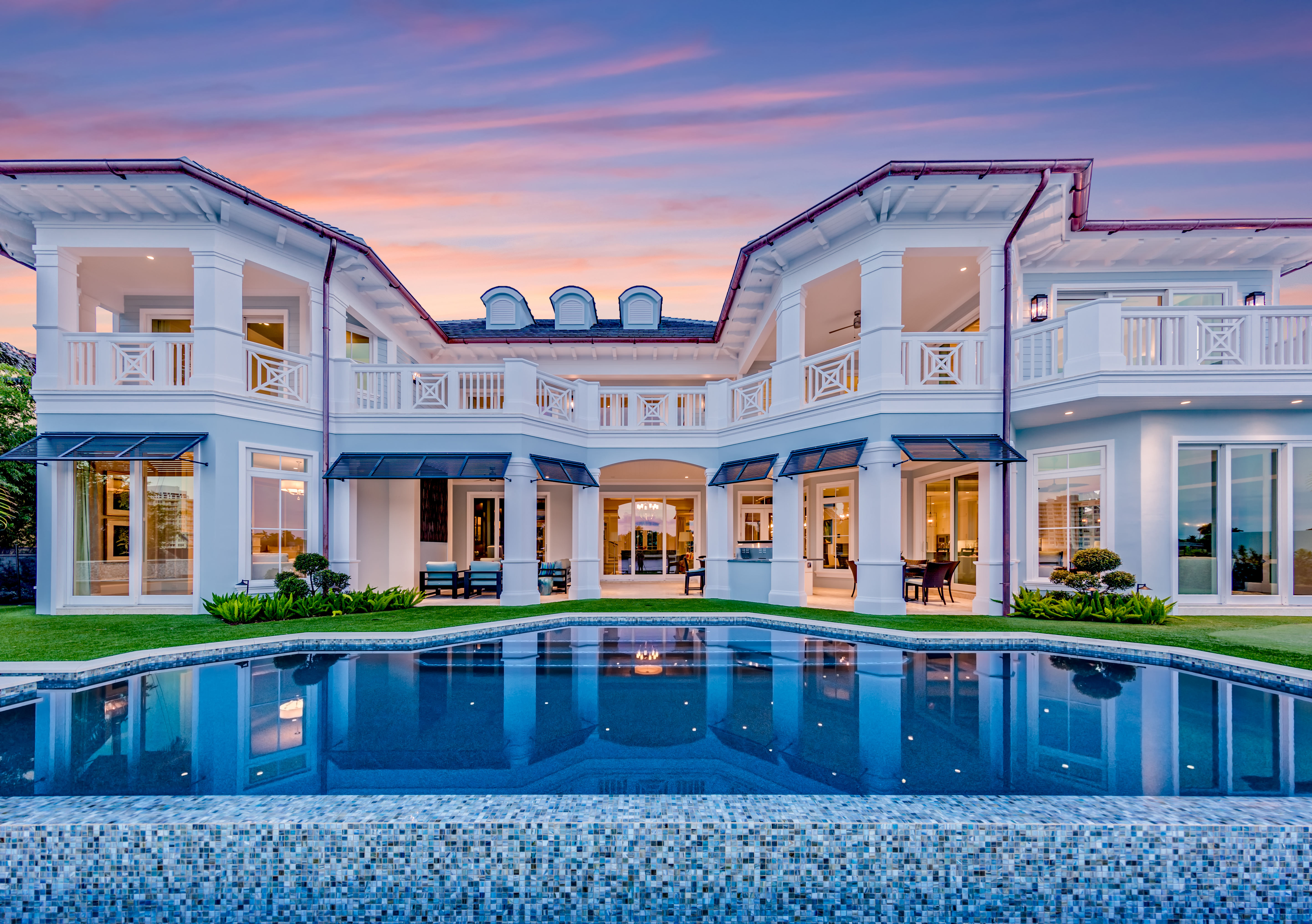 A magnificent mansion in fort lauderdale with the sun setting in the background and an infinity pool in the foreground
