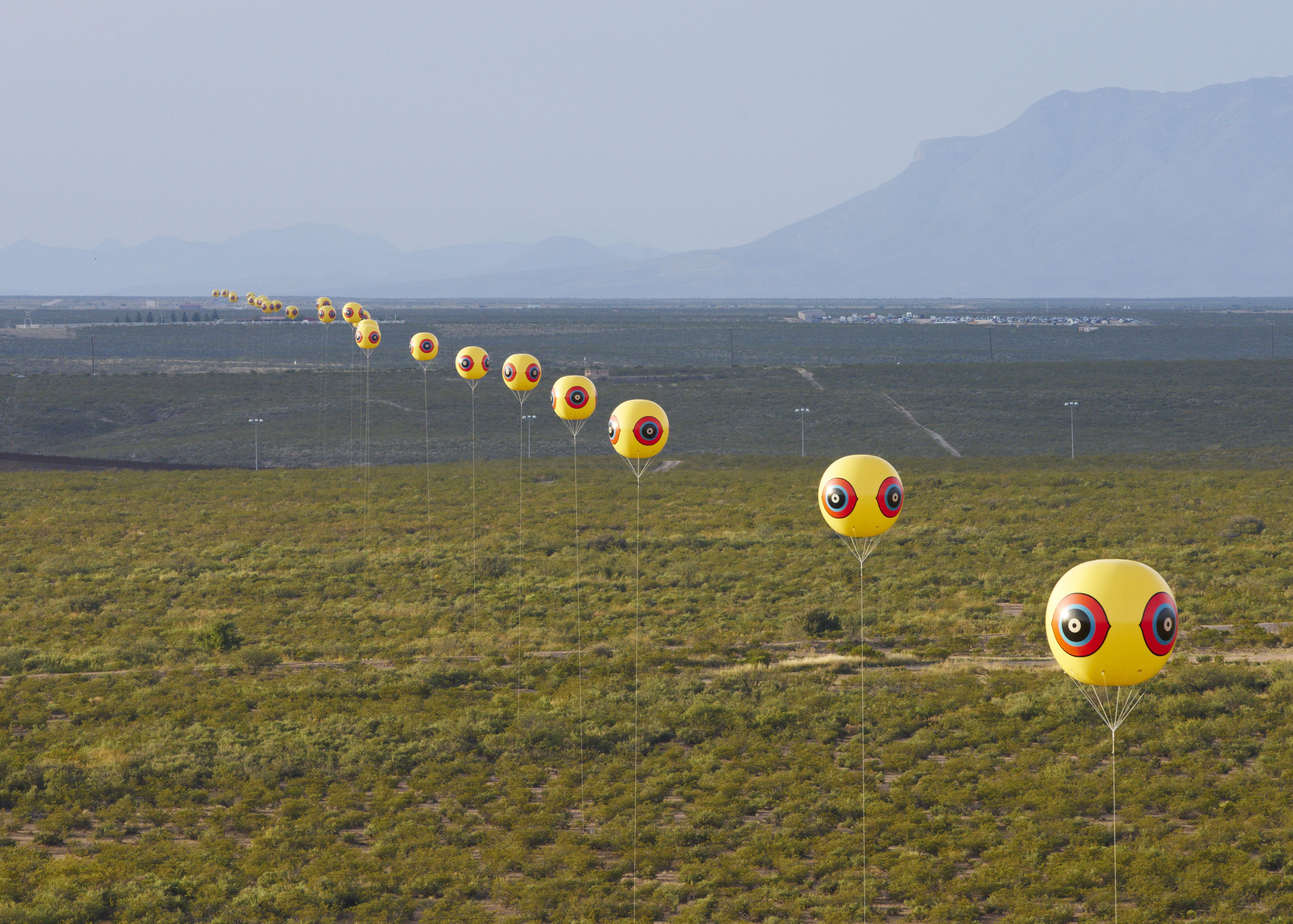 Eyeball balloons placed in a line across a desert