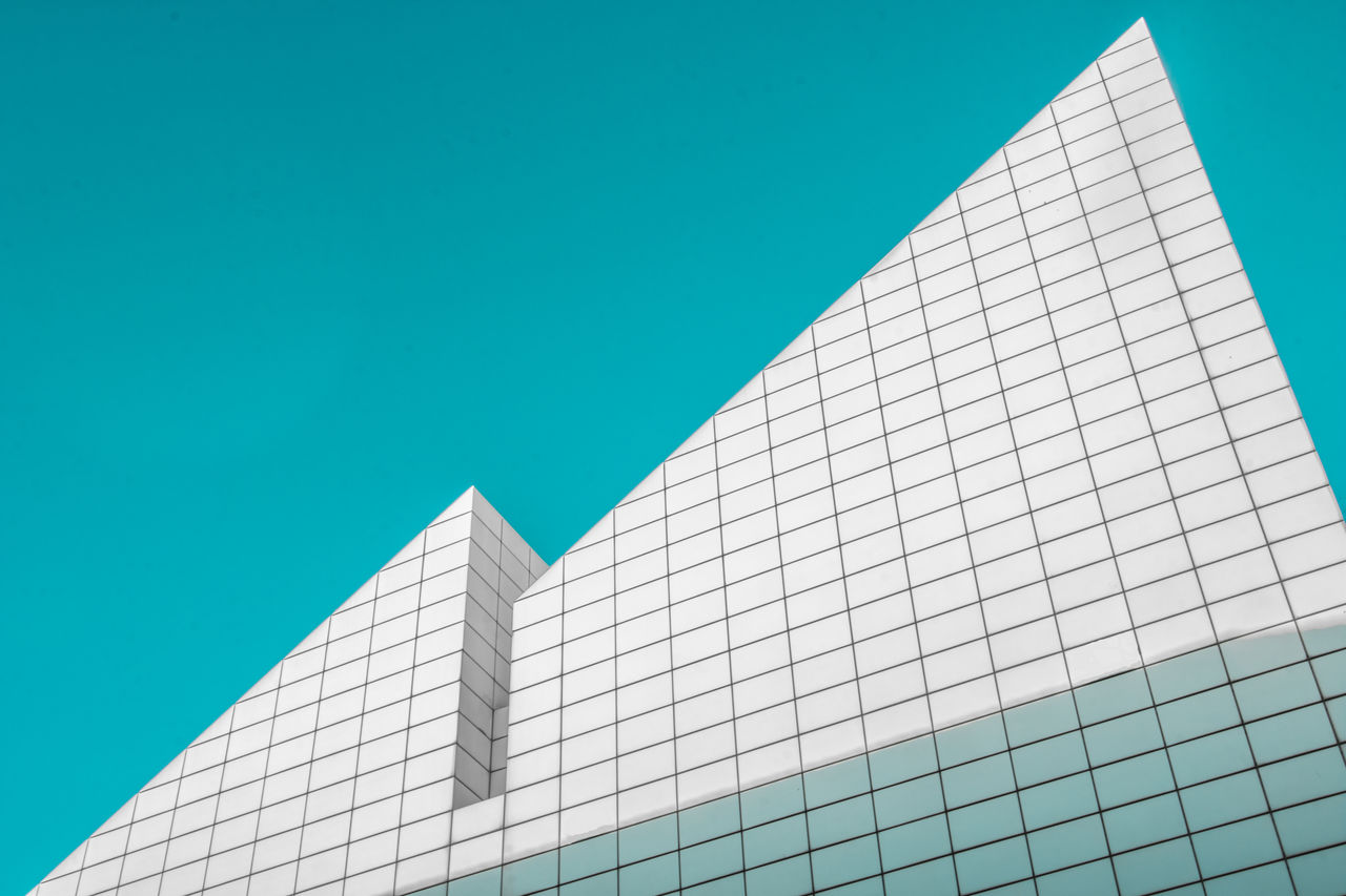Abstract photo of two triangular points of a white, gridded building against an azure blue sky.