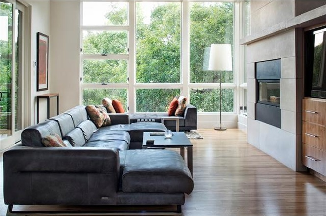 two-story contemporary living room with fireplace and wall of windows