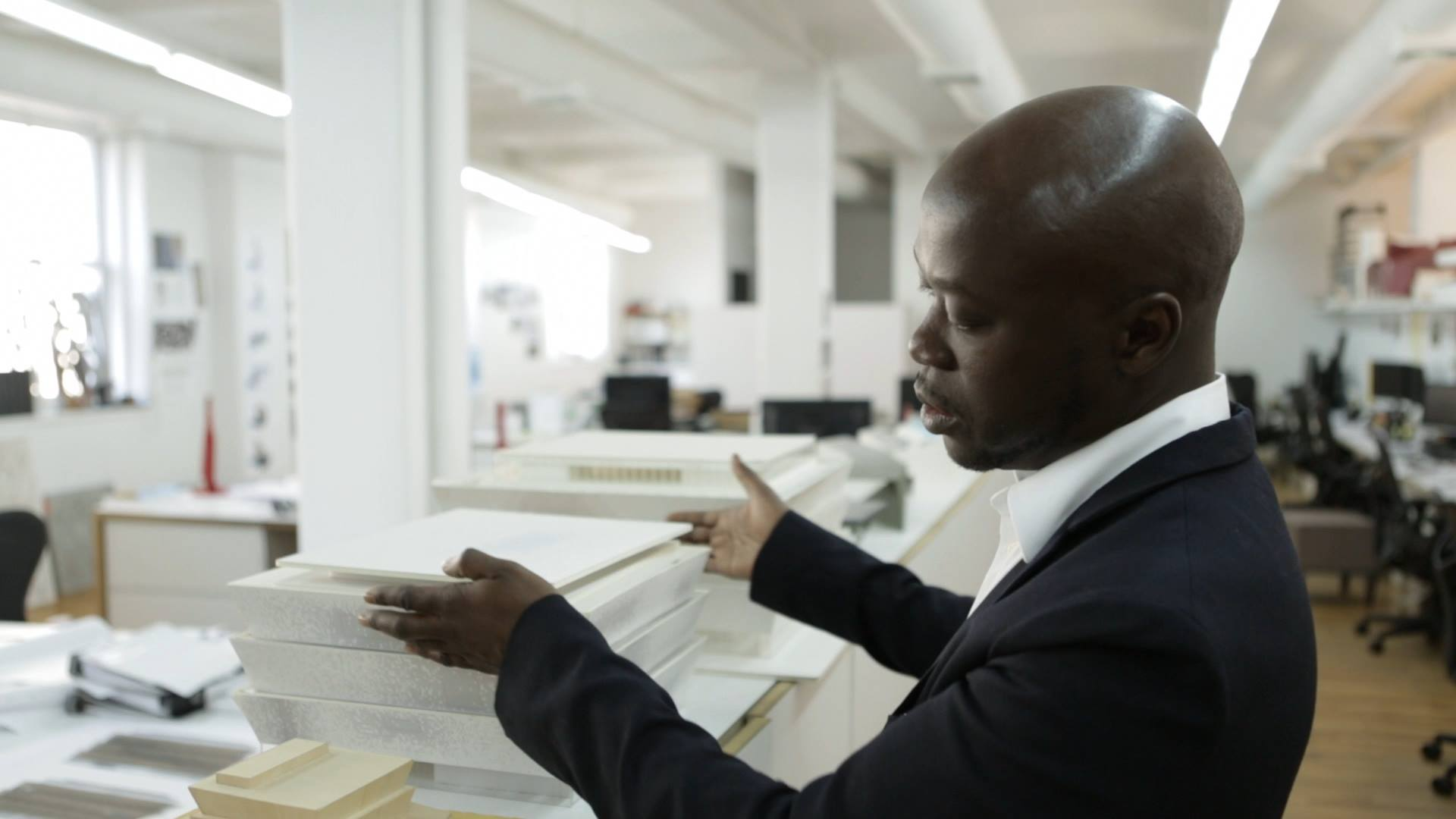David Adjaye arranging a stack of white blocks on a table with offices in background