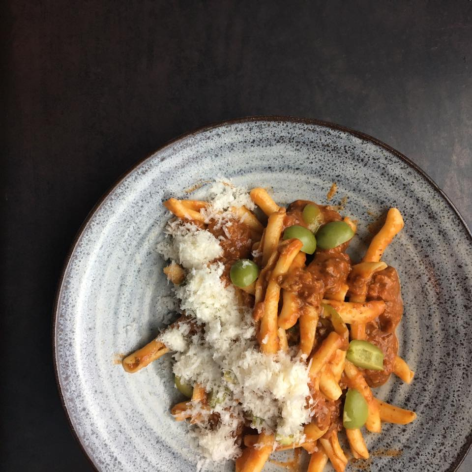 Bird's-eye view of duck bolognese with strozzapretipasta.
