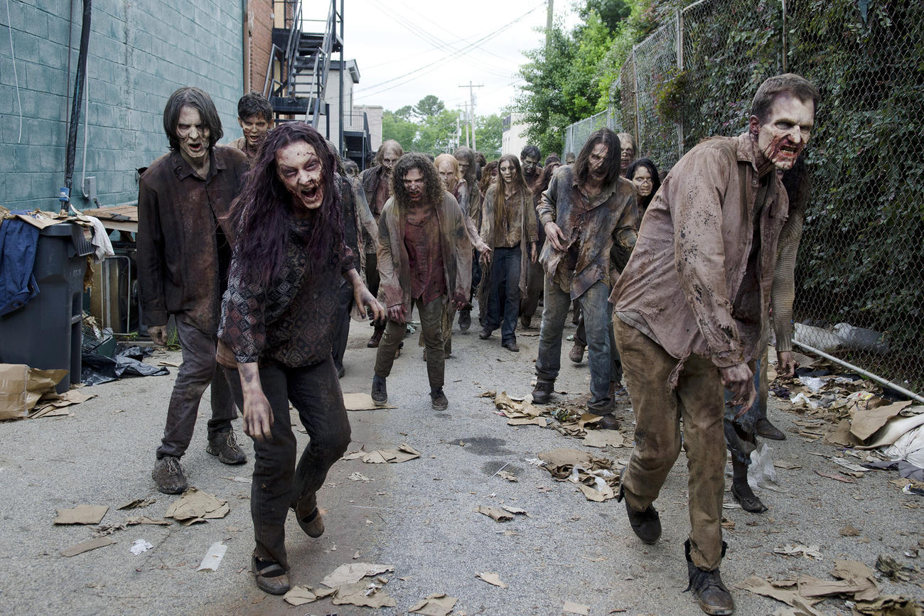 Actors and actresses in the show The Walking Dead are in zombie makeup and tattered clothing while walking down a street next to a blue building.