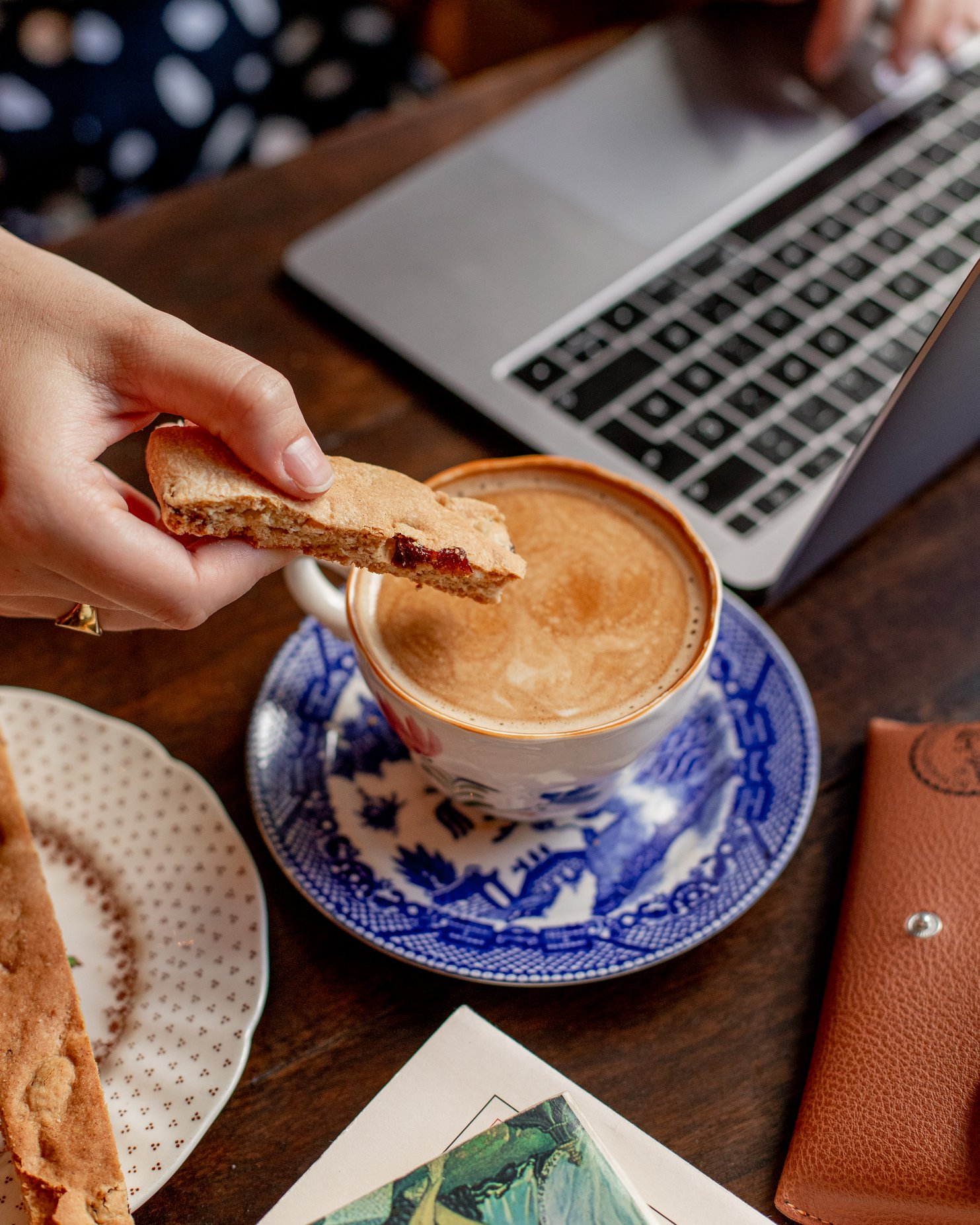 dipping cookie in coffee with laptop in the background