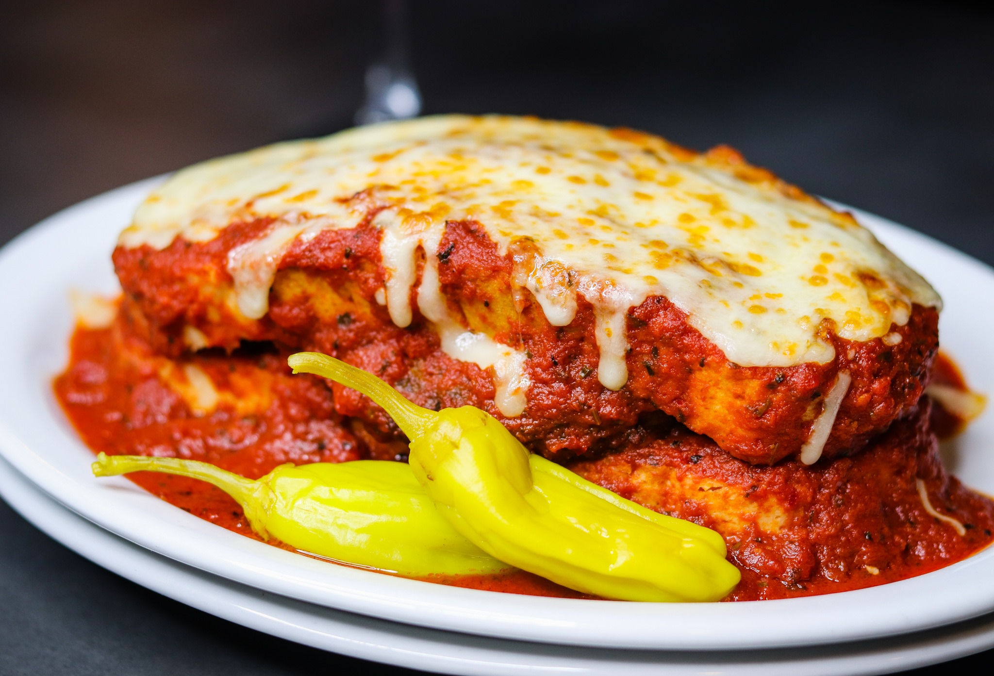 A sliced open Italian sausage is buried under red sauce and covered with a layer of toasted, melty white cheese in a plate filled with sauce and two pepperoncinis.