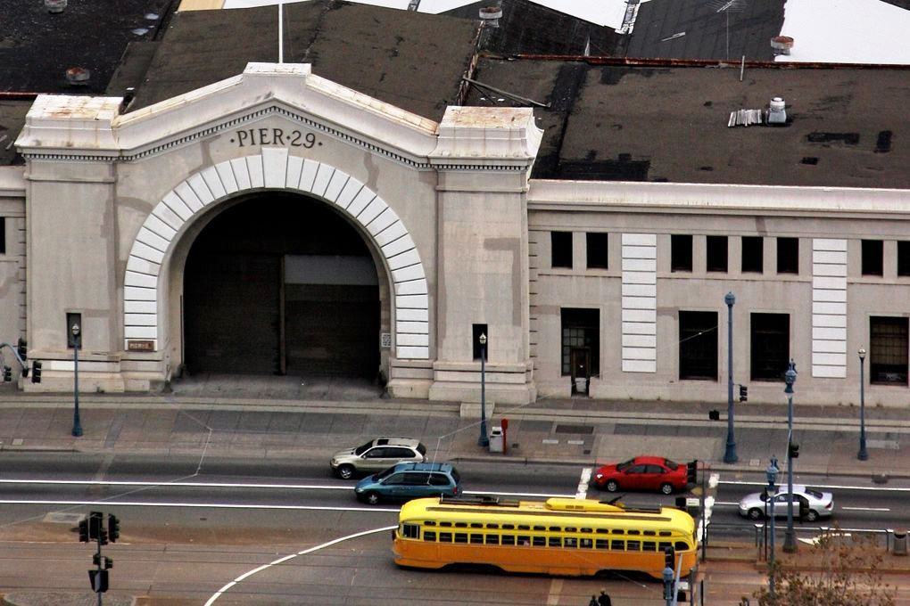 A yellow streetcar rolling by the bulkhead building at Pier 29.