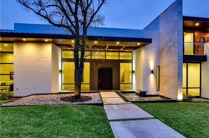 Contemporary home entrance, concrete, flat roof, big window walls, lighted from inside, dusk