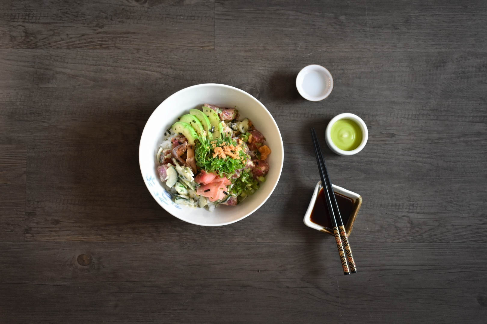 Overhead view of a bowl of poke with chopsticks and dishes of condiments.