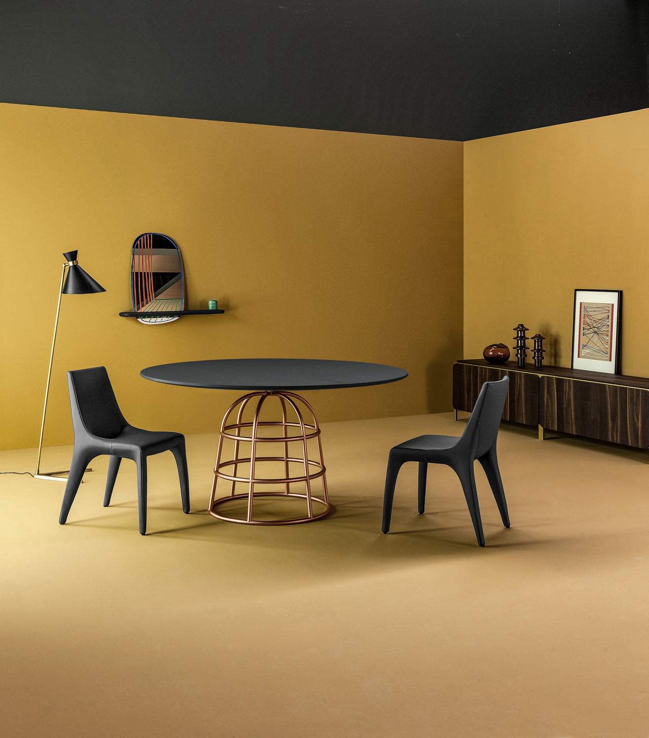 Showroom shot of a dark round table with a gold, metallic base in the shape of a birdcage surrounded by two black plastic chairs in a mustard-colored room. A conical floor lamp and a low credenza complete the scene.