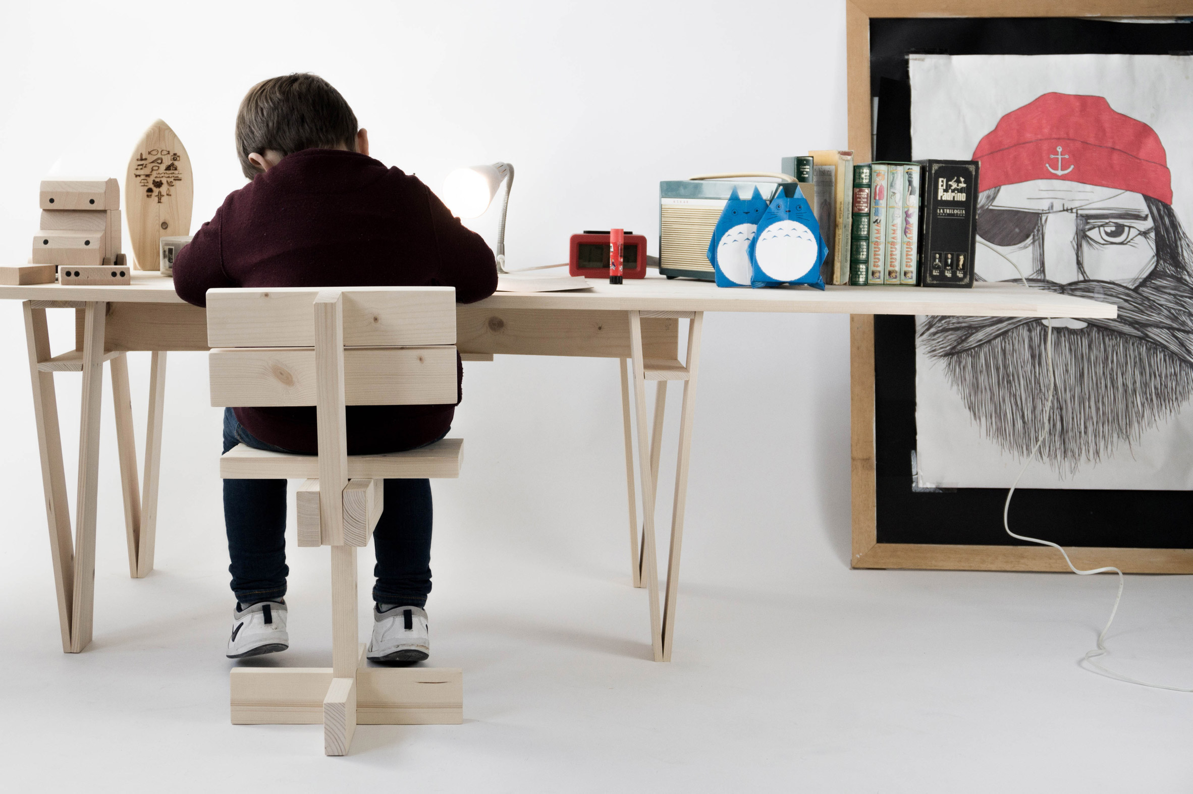 Shot of small child sitting at a wooden desk in a simple chair made of wooden planks.