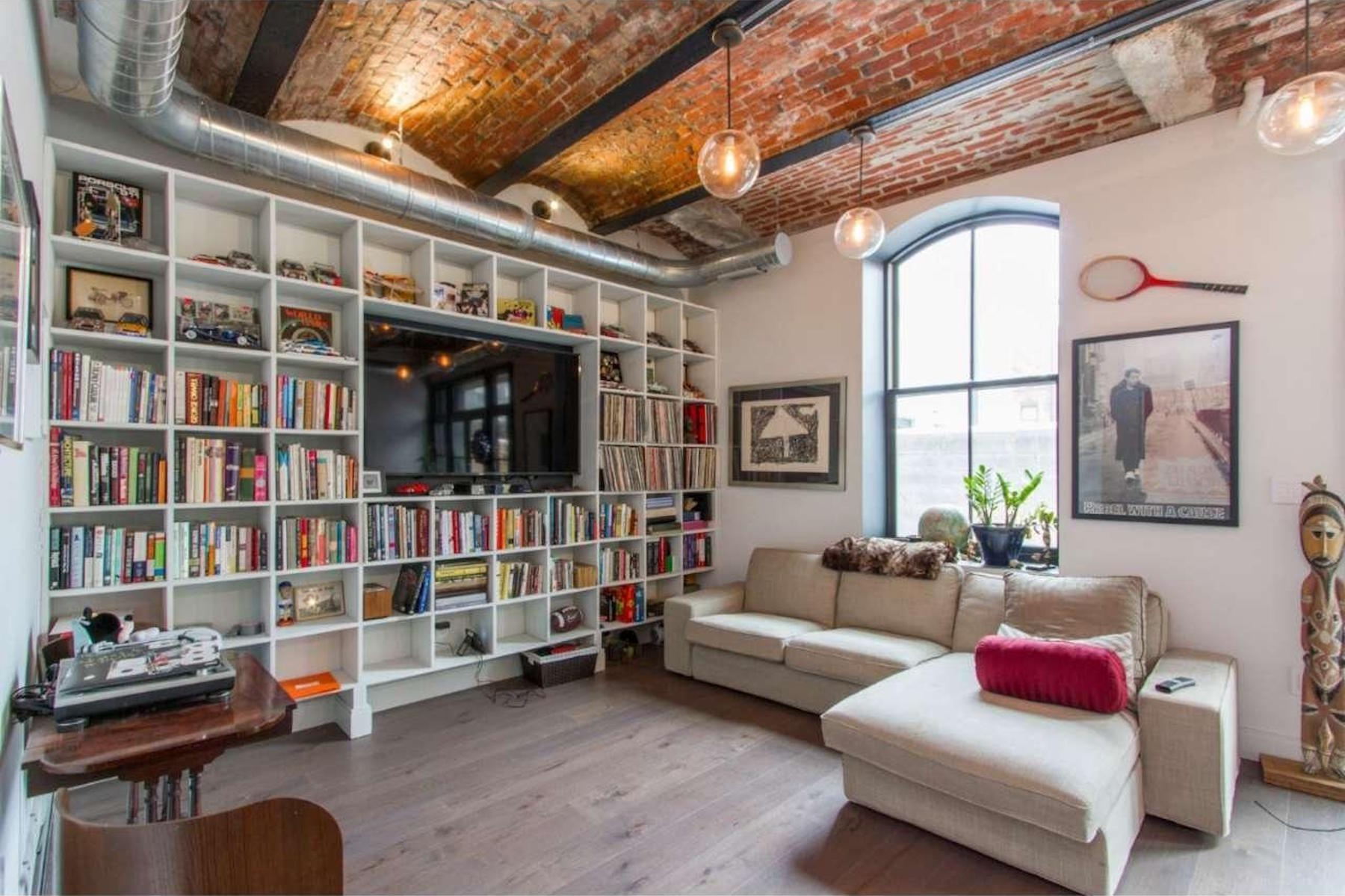 A living room with a wall of built-in bookcases and brick barrel ceilings.