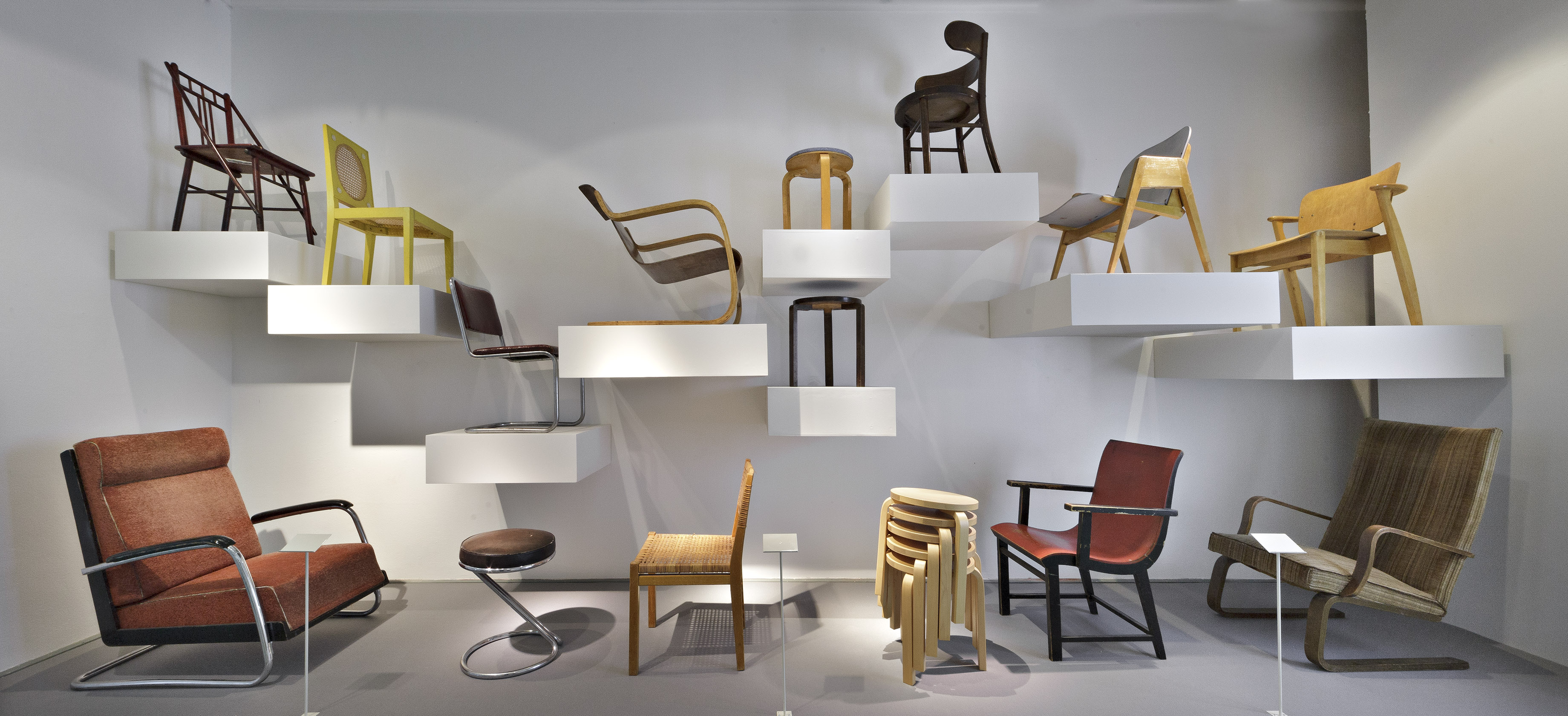 A collection of chairs at the Design Museum in Helsinki. The chairs are all different and are positioned on shelves of varying heights.