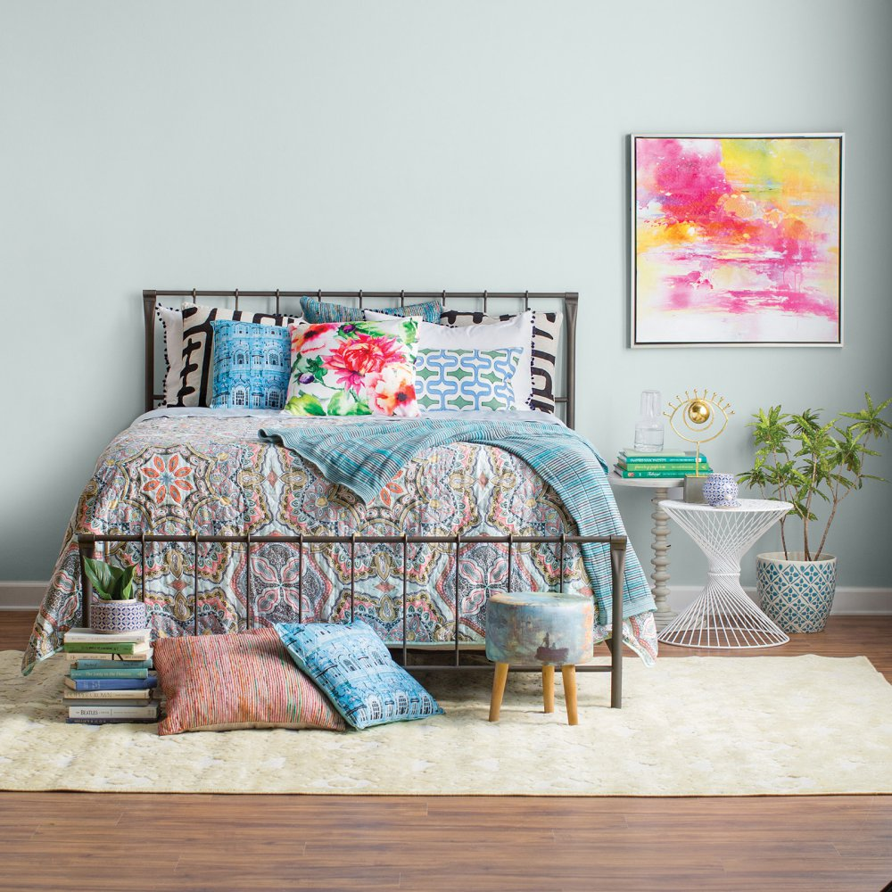 Bedroom scene with steel-framed bed with headboard and colorful bedding and pillows.