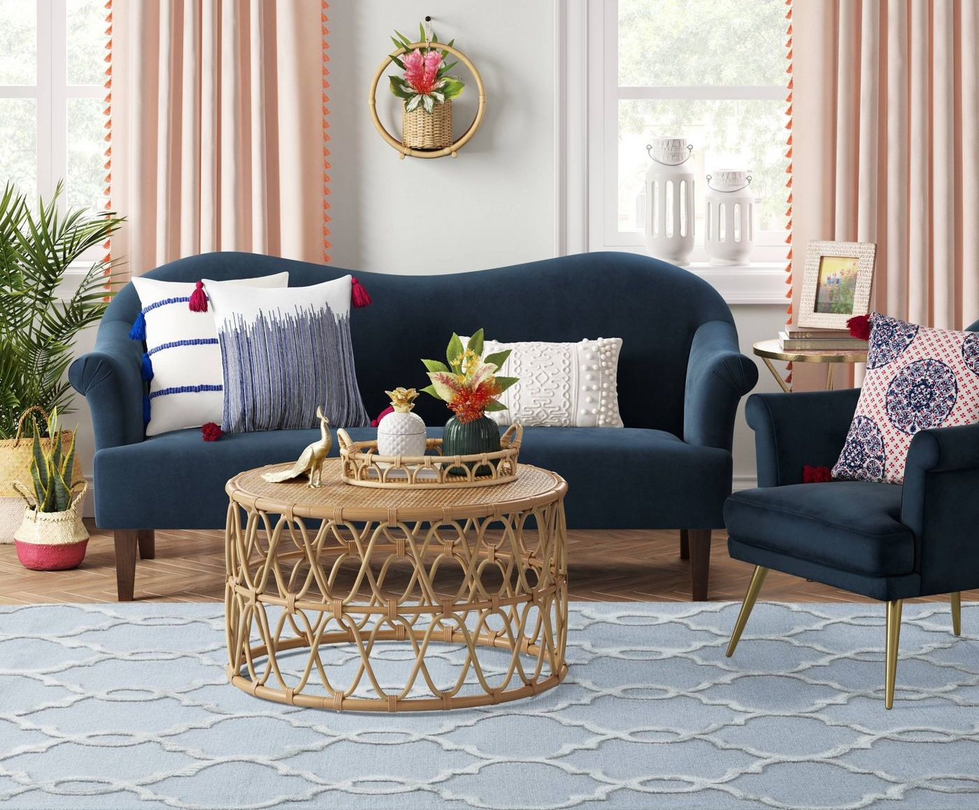 A living area with a patterned area rug, wicker table, chair, couch, and windows.