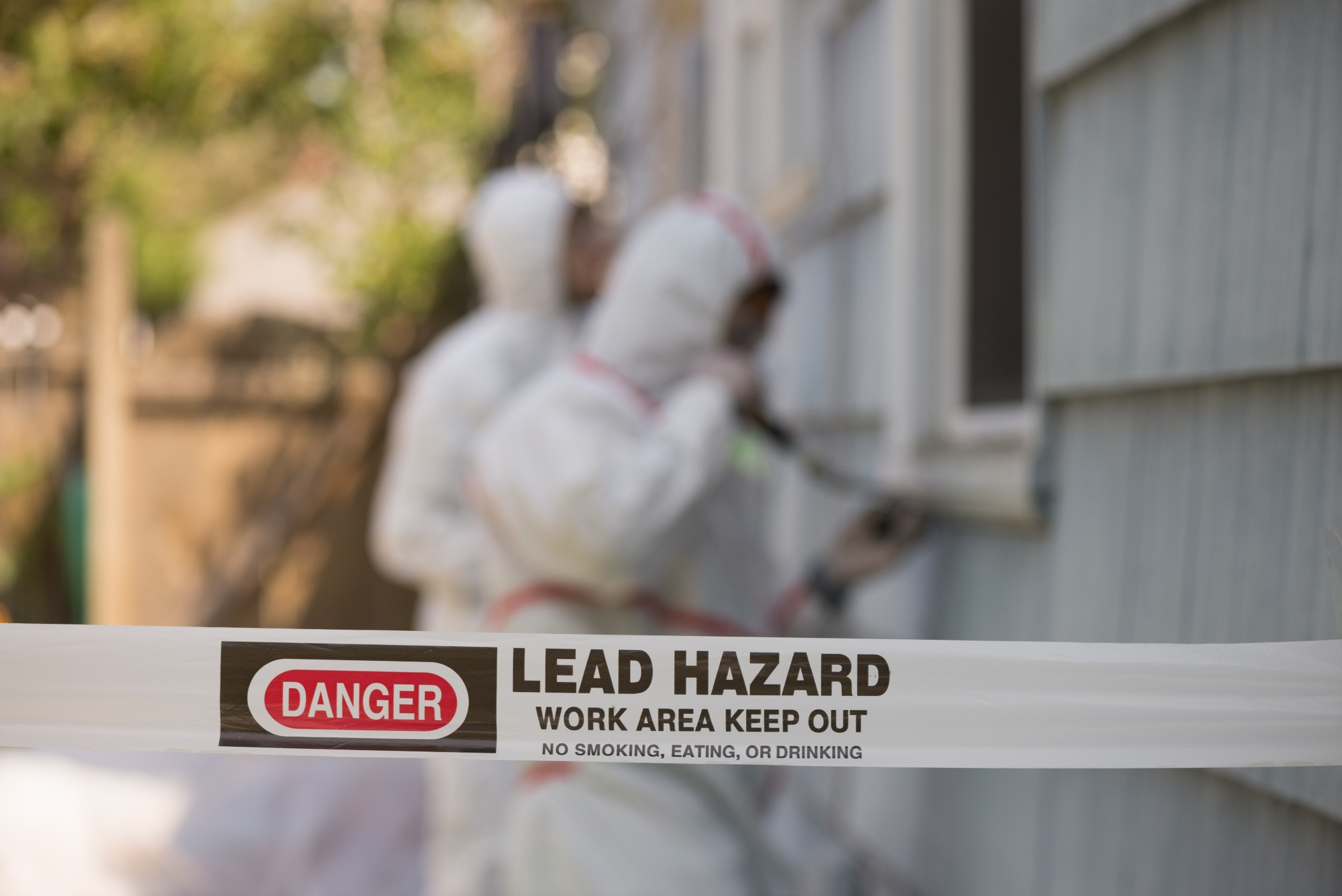 """Workers in hazmat suits stripping old paint from a house. Caution tape in the foreground warns: """"Lead Hazard."""""""