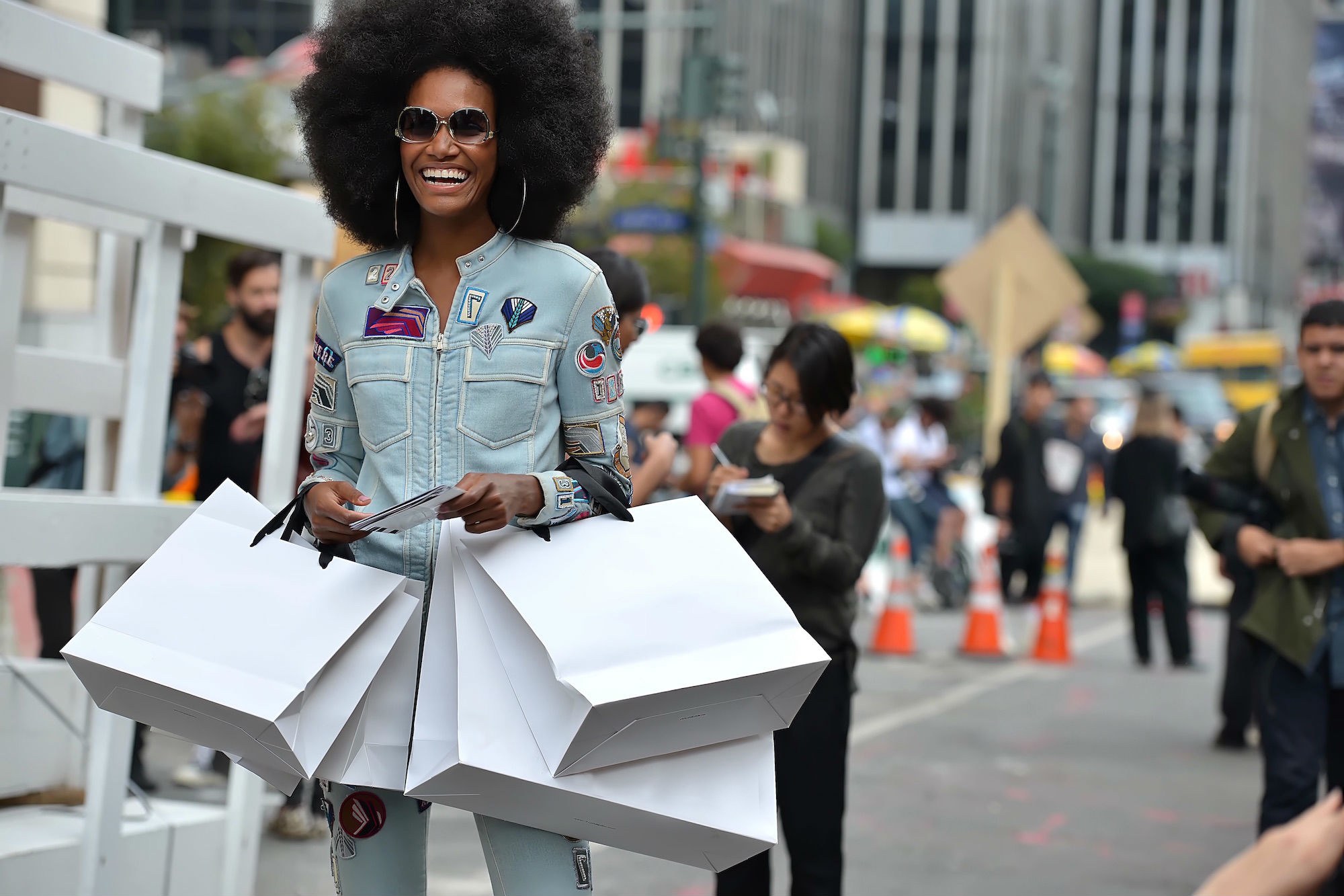 A woman carrying a bunch of white shopping bags standing outside