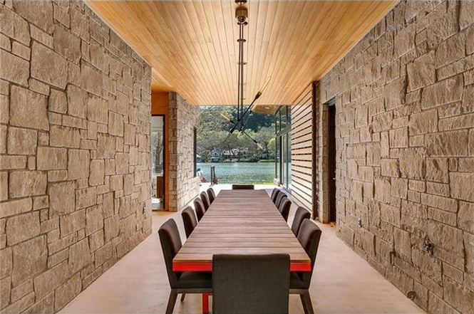 Modern dogtrot/breezeway with stone walls, wood ceiling, long dining table, lake view at end
