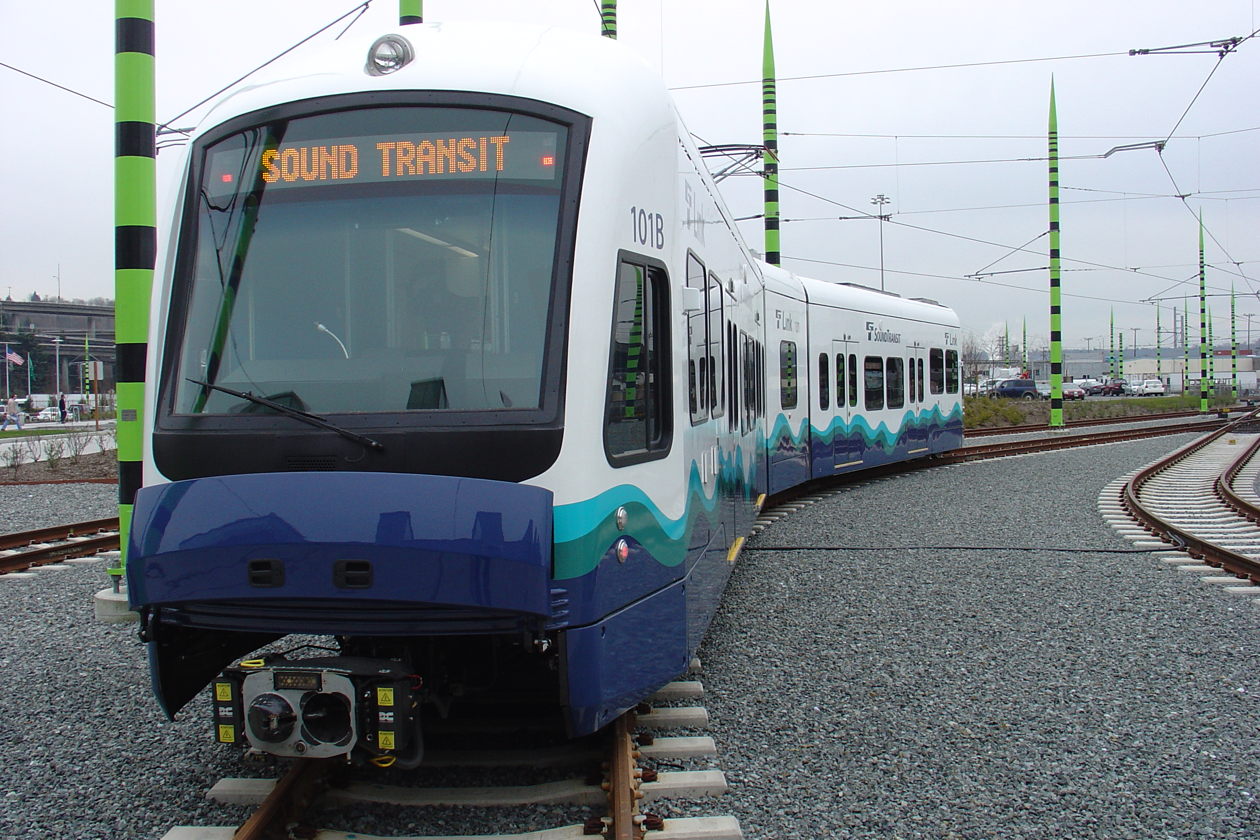 """A light rail train with blue, green, and teal details. The LED reader on the front says """"Sound Transit."""""""