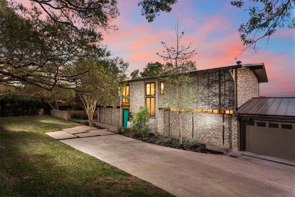 Large two-story ranch-style/midcentury home with stone walls and big windows