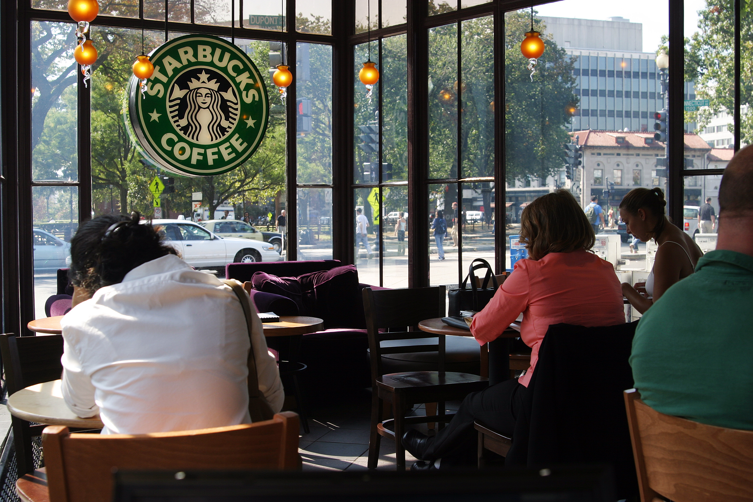 People drinking coffee inside a Starbucks midday