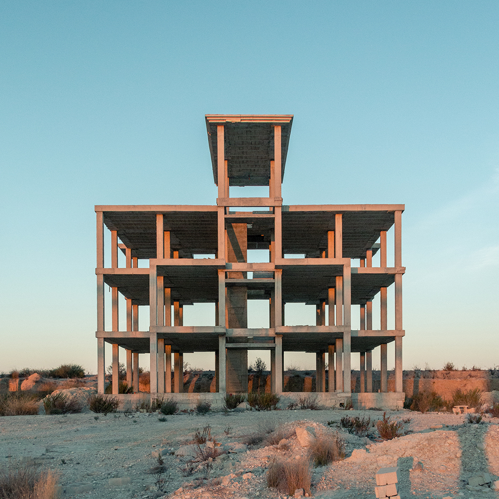 A concrete frame rises in the sand.