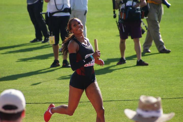 A smiling woman with a relay baton in black track uniform with a bunch of dudes in background, green grass