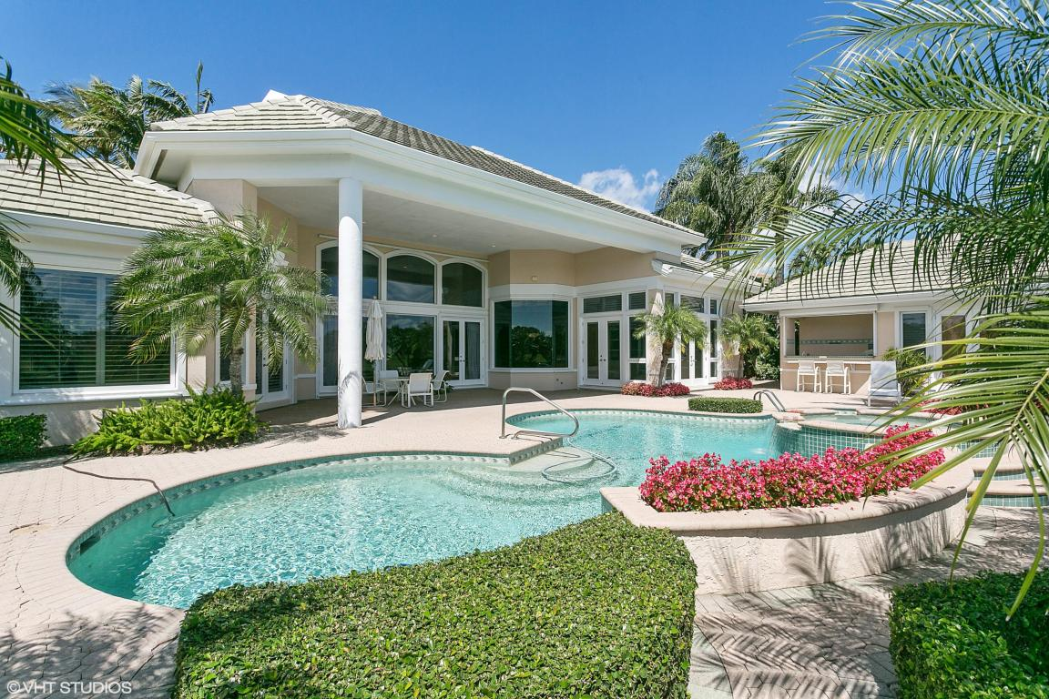 A Florida home with a large column in between the pool and the outdoor living area with a barbecue nearby.