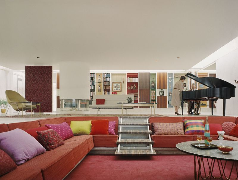 View of a retro white living room with square depression in ground lined with red sofas and colorful cushions with steps leading into it from the main floor.