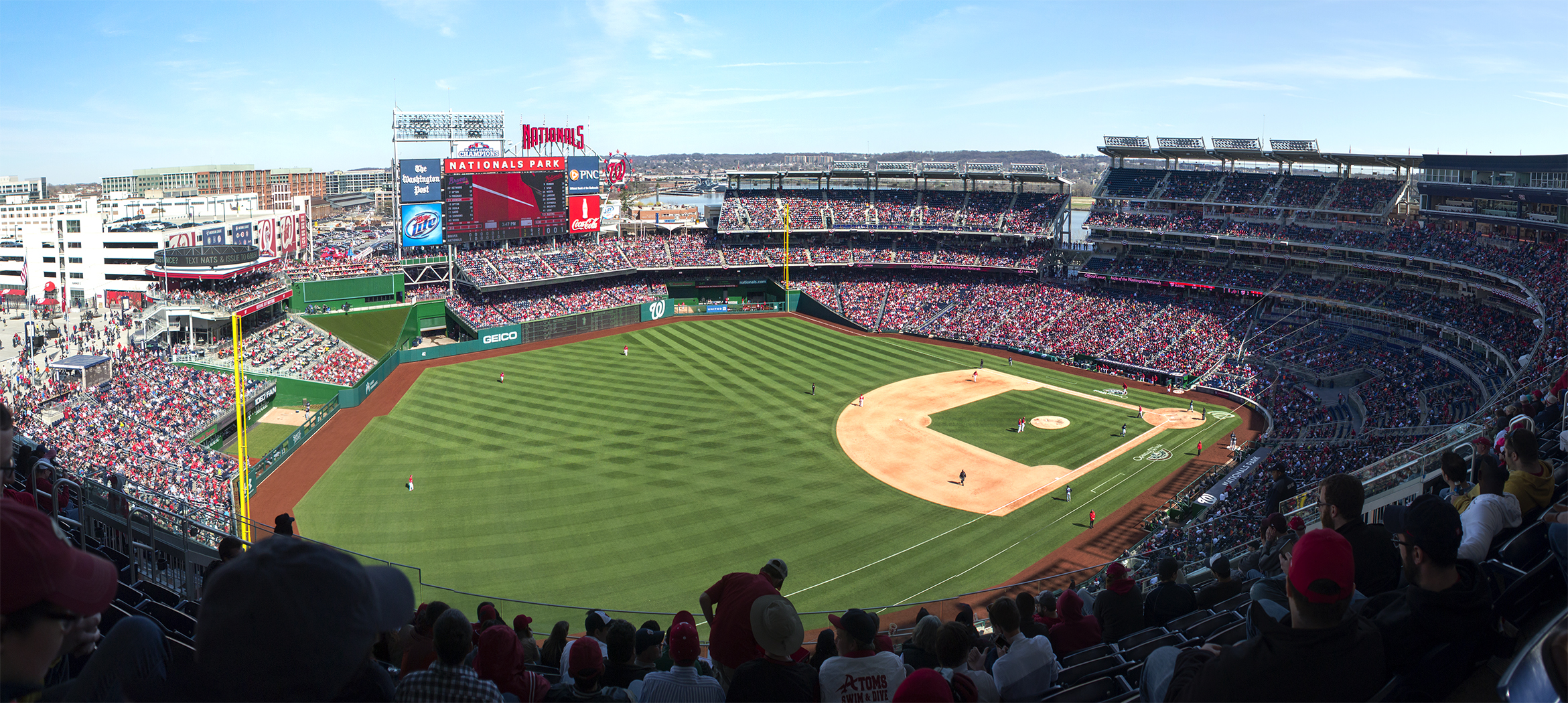 The inside of a baseball stadium. There are billboards and many fans sitting in the background.