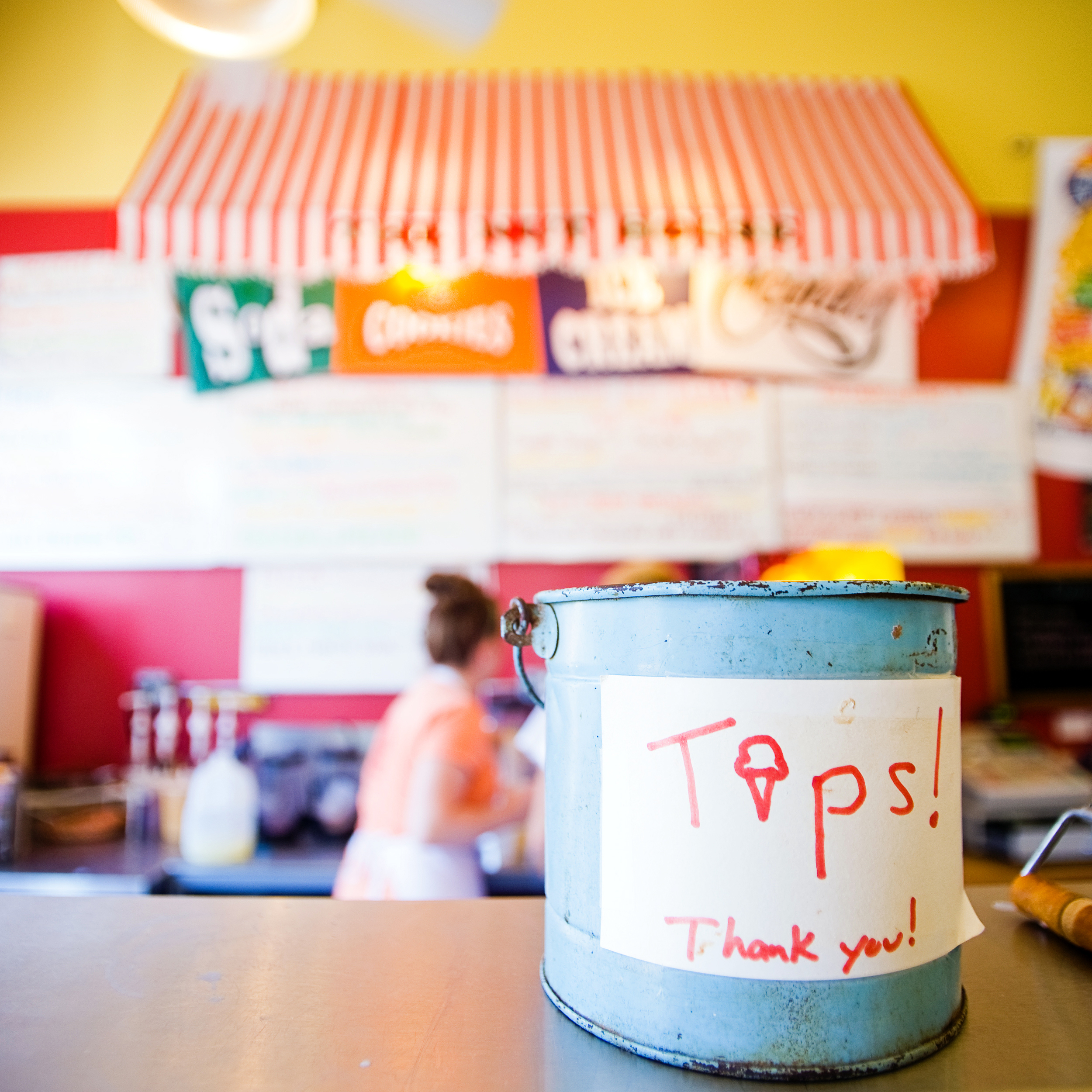 "A blue can at a cafe with a paper sign taped on it reading ""Tips! Thank You!"" The ""i"" in Tips is shaped like an ice cream cone."