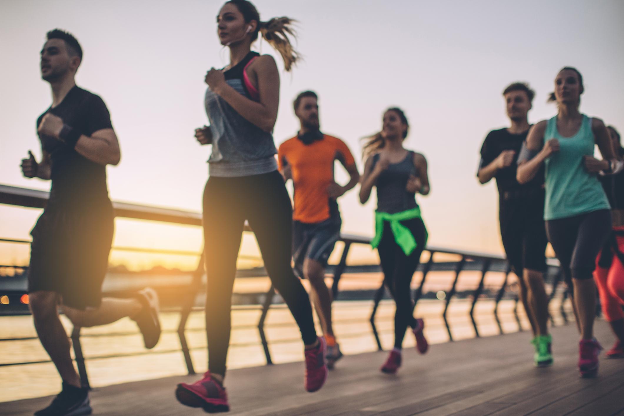Runners running across a bridge with bibs on