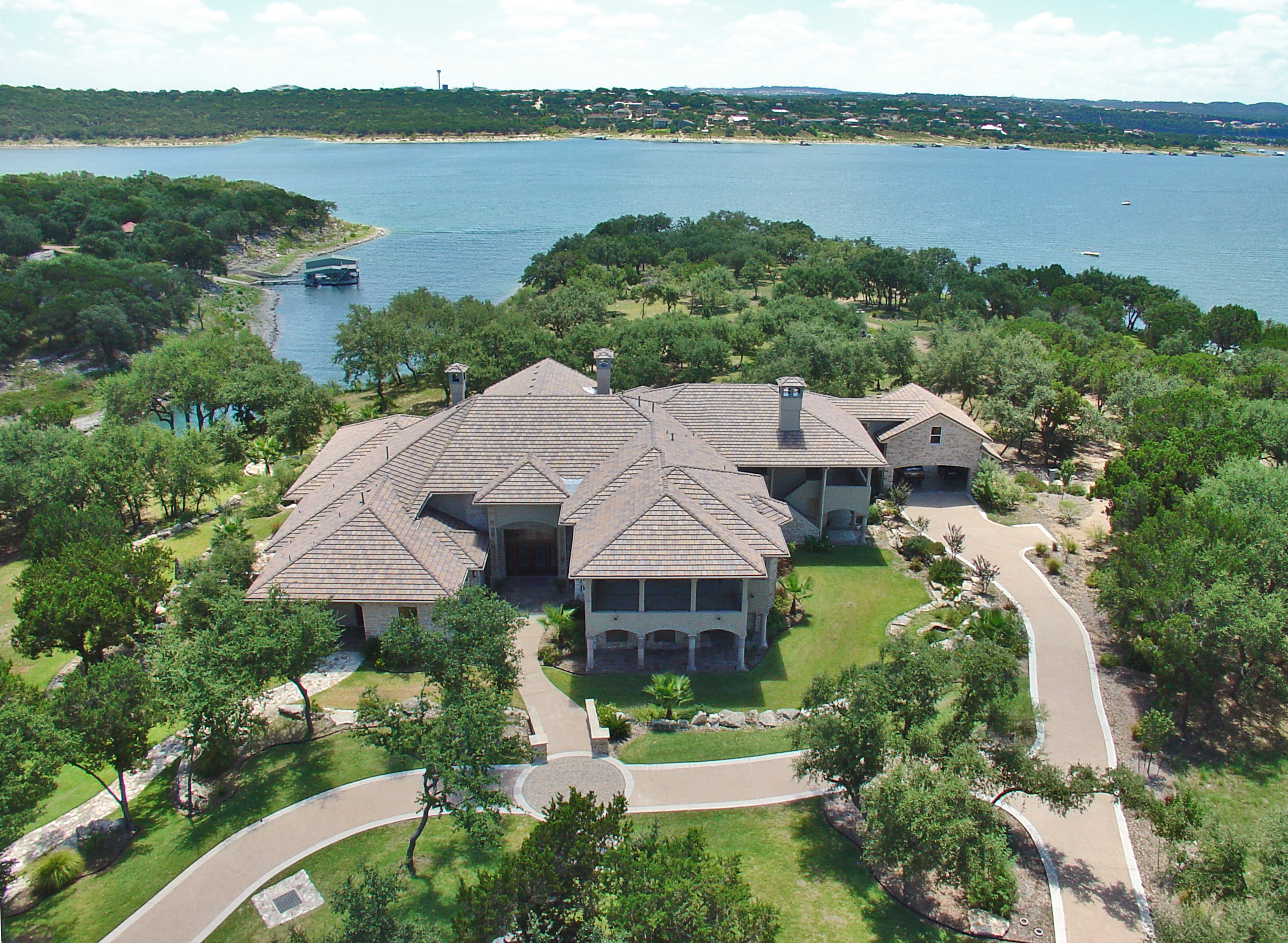 Aerial view of very large, two story mansion compound on green peninsula with lake in background