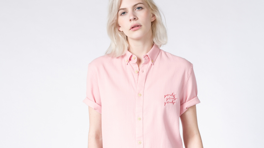 A model wearing a pink shirt that says Girls Girls Girls on the chest