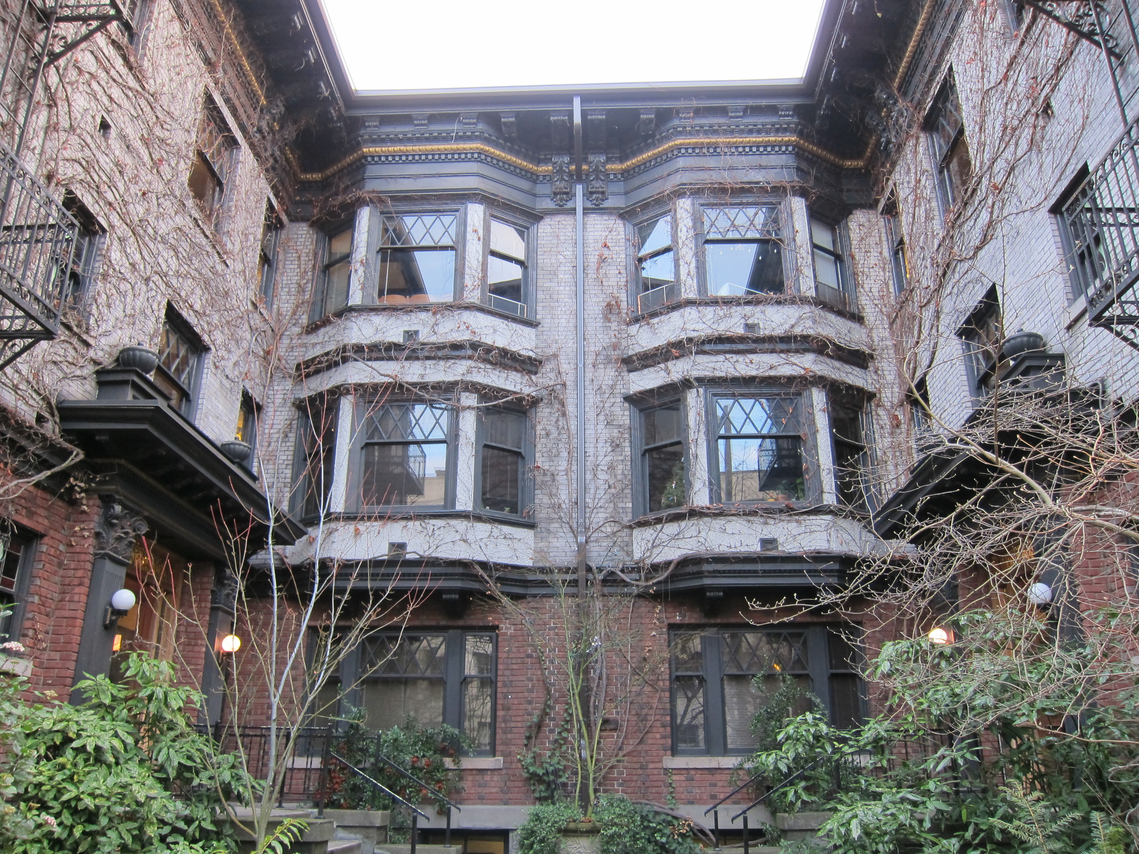 An apartment building with bay windows, viewed from inside a courtyard.
