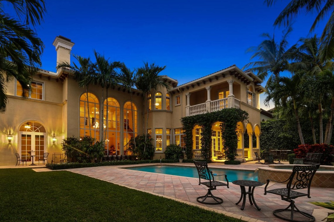The backyard view of a large home in palm beach