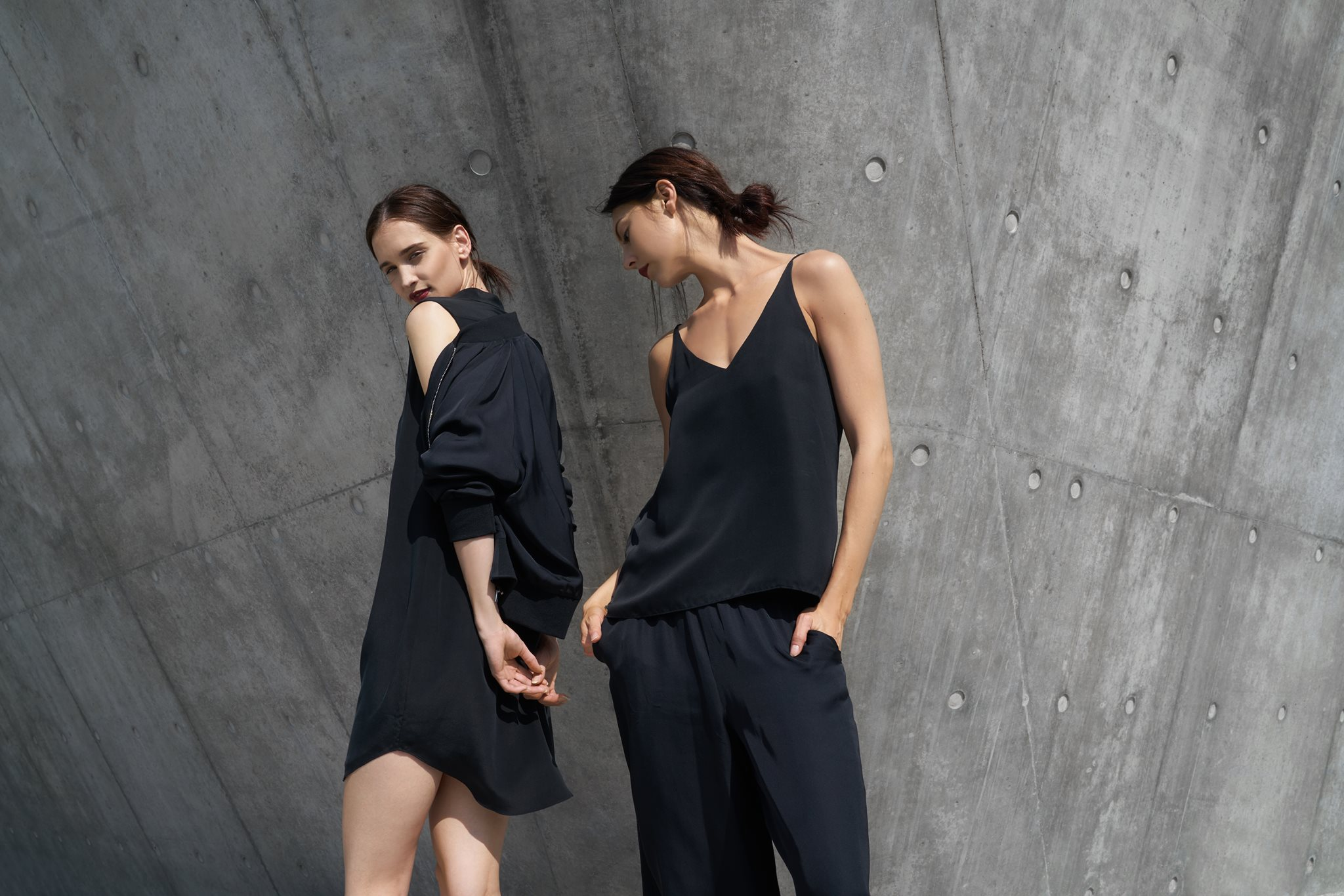 Two women wearing black silk standing in front of a gray wall