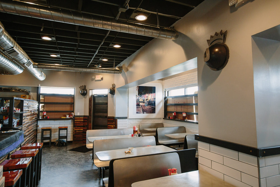 The interior of Johnny Noodle King has fast-food type tables, a bar with reclaimed wood on the exterior and red stools, and white subway tile on the walls.