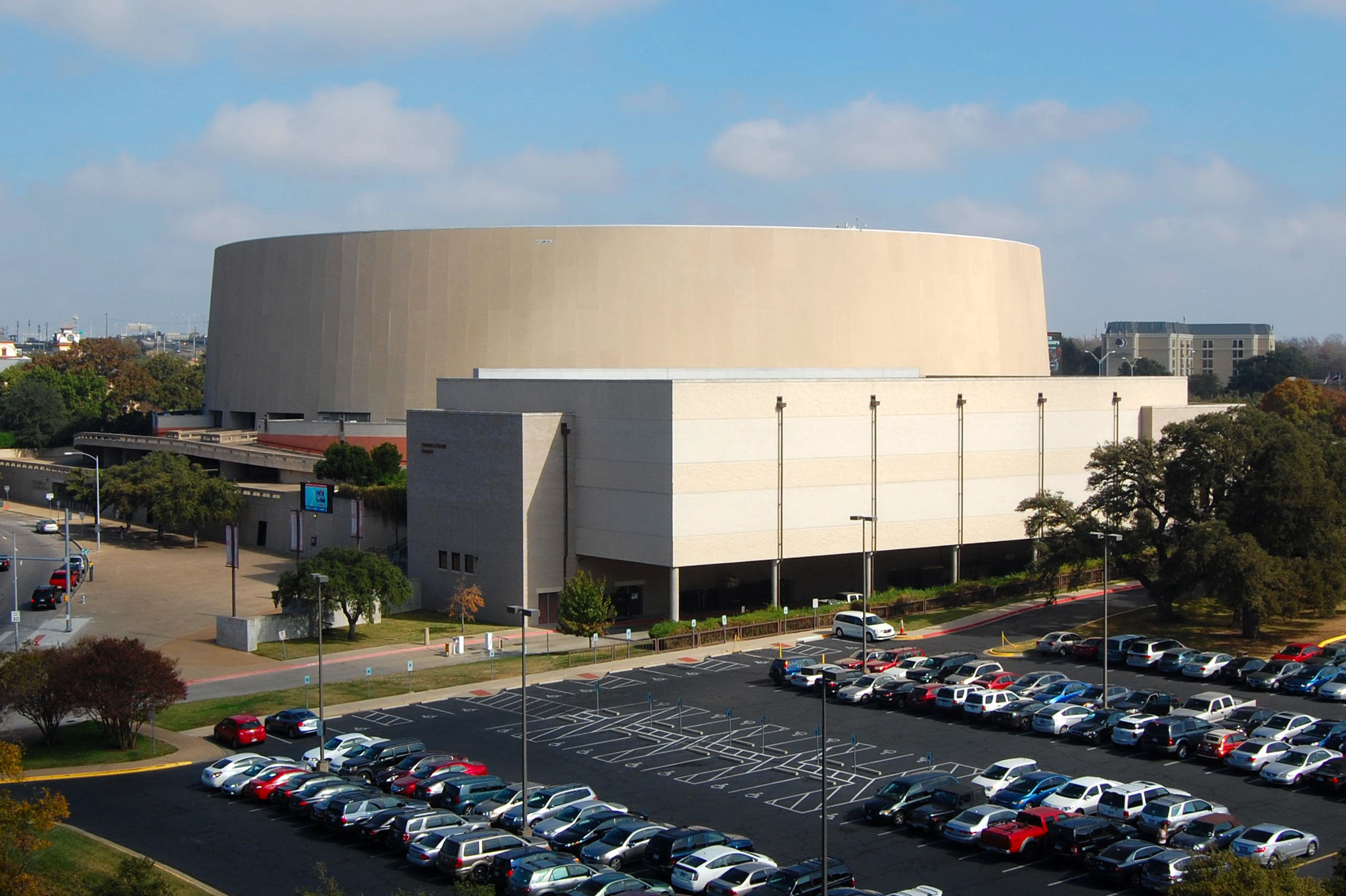 Large, round, windowless building with parking lot and garage in front