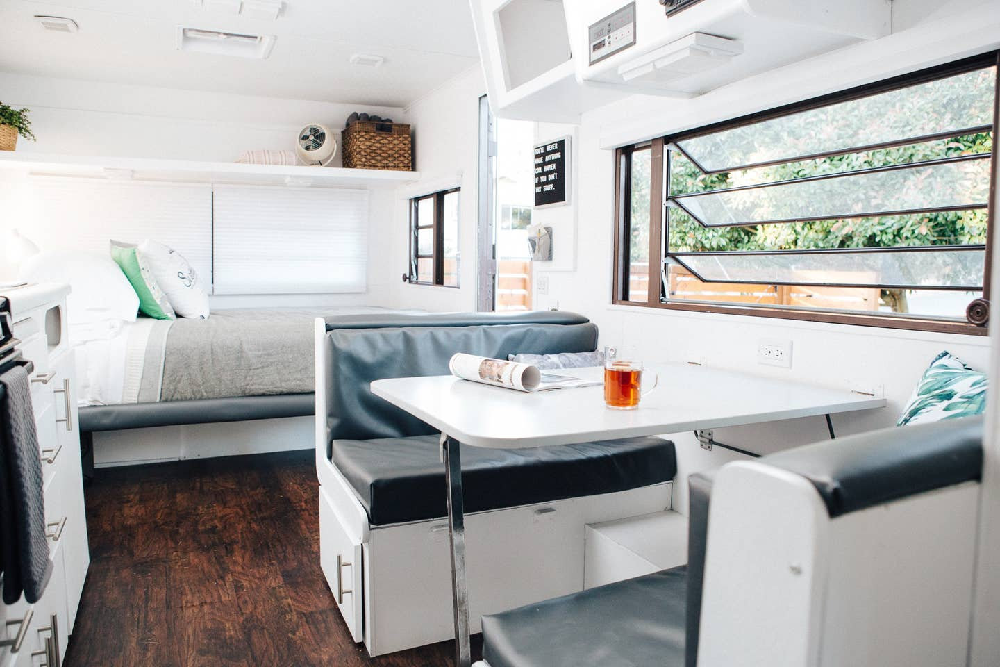 The inside of a trailer with all-white walls and shelves has a dinette along the right wall with a window above and a full-size bed built into the far wall.