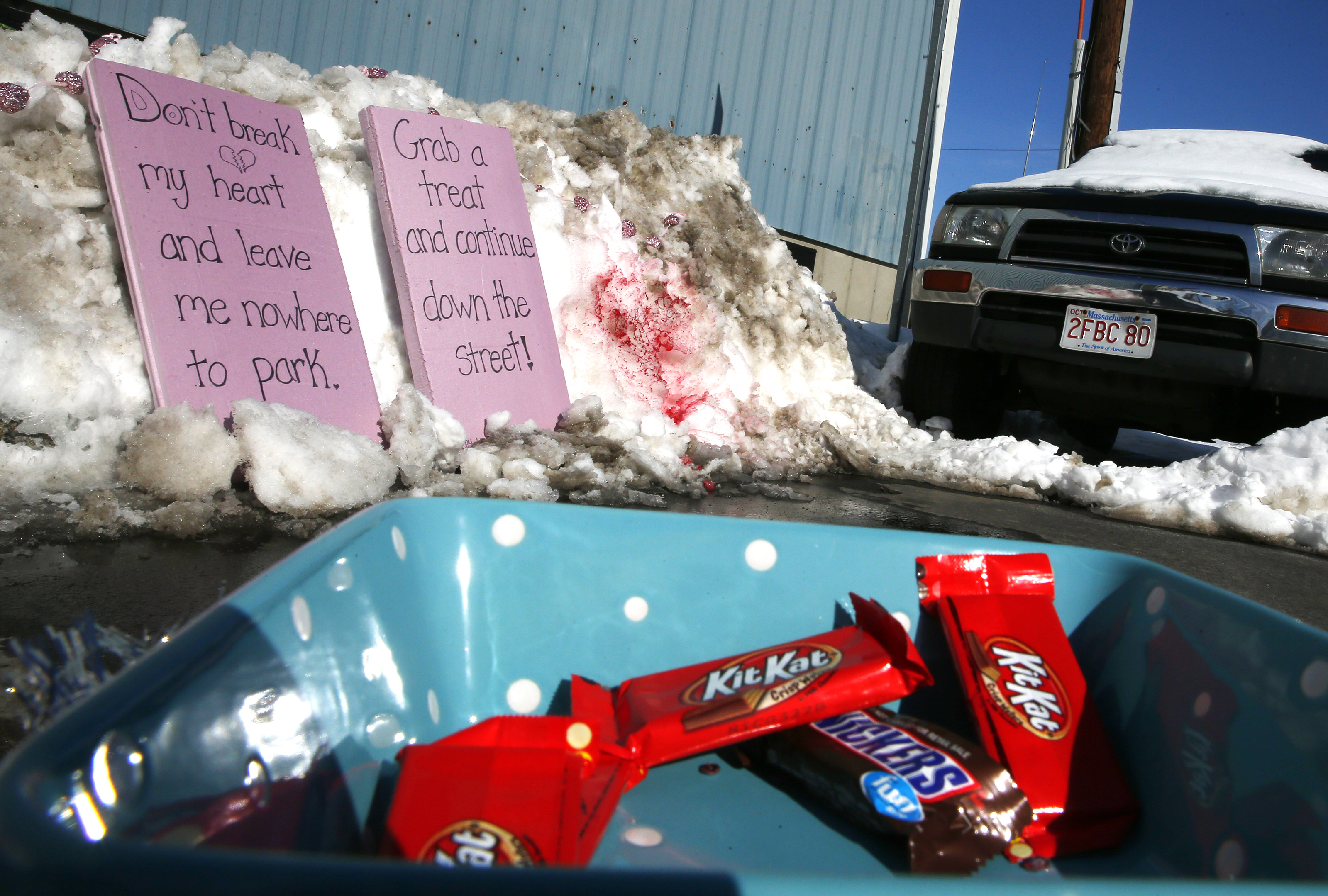 Funny signs leaning against a snow bank telling people to move on from a parking spot that's occupied by a wheelbarrow full of candy.