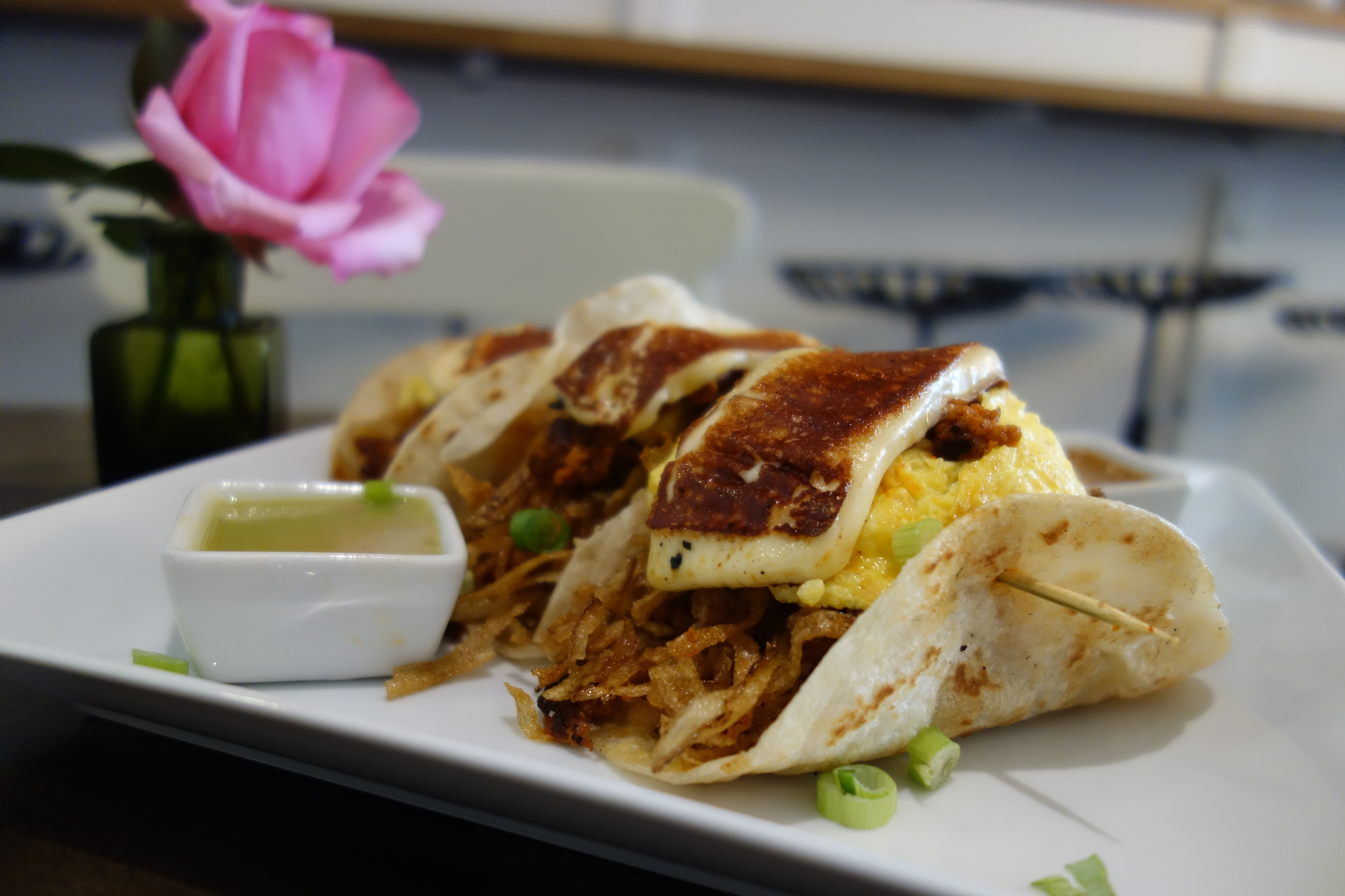 Three breakfast tacos with dipping sauce
