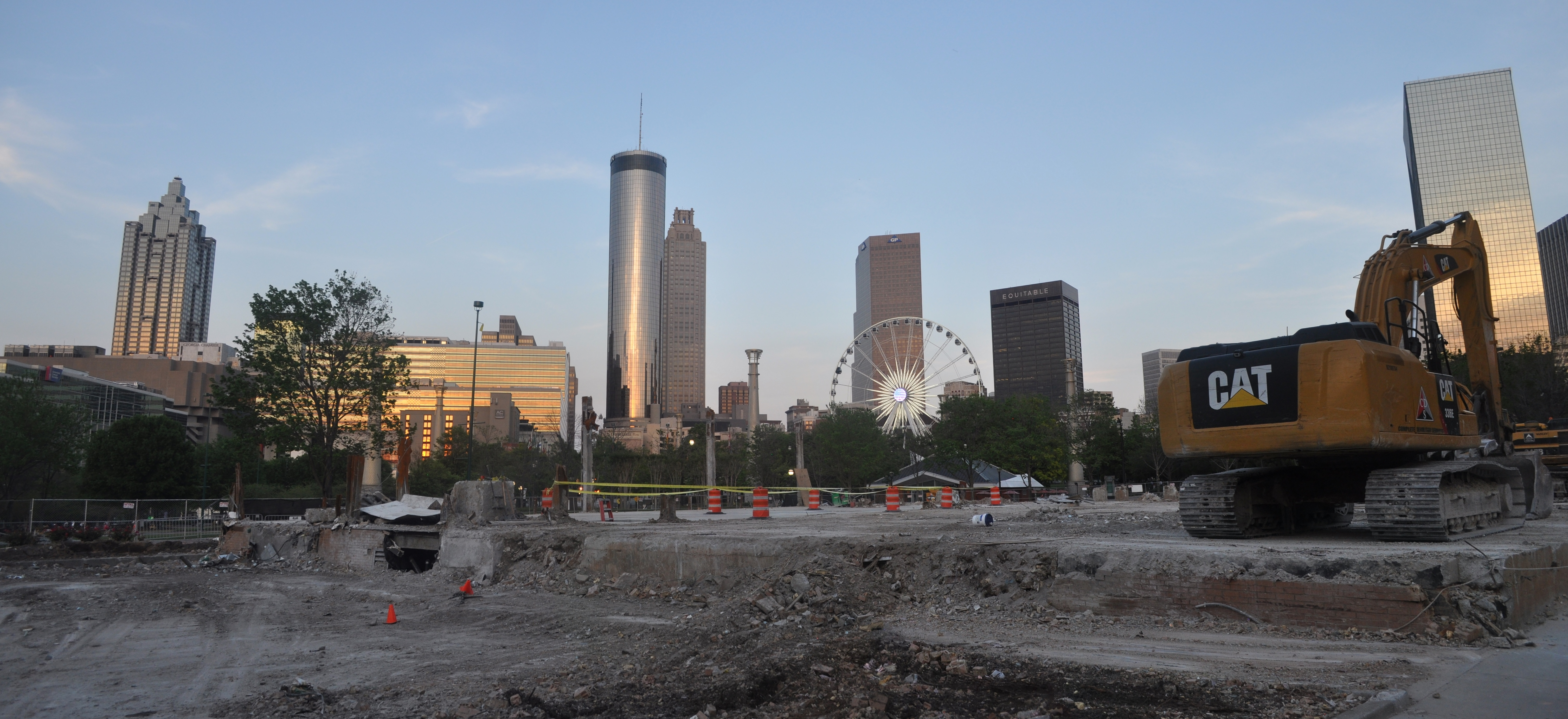 An excavator sits on the concrete slab of the old building, with the skyline and Ferris wheel in the background.