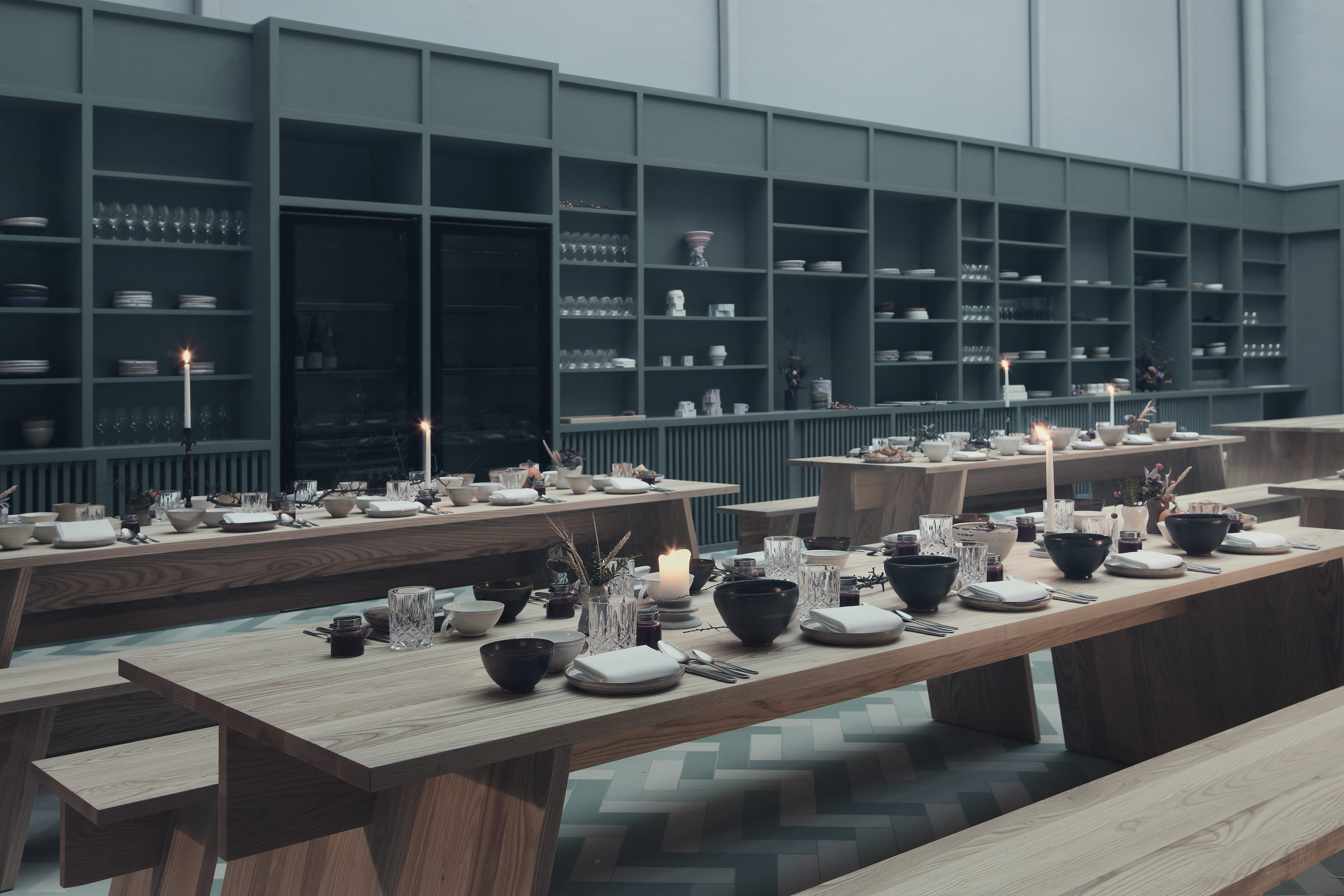Interior shot of atrium with wall lined with dark shelves and wooden picnic-style tables topped with table settings arranged in two rows.